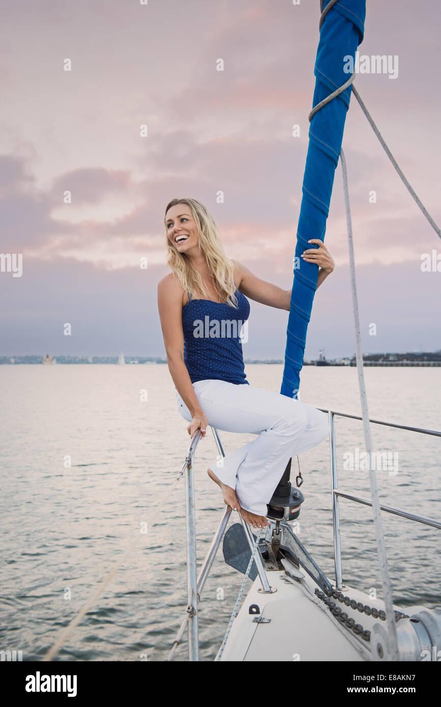 Jeune femme assise sur main courante sur bateau à voile Photo Stock