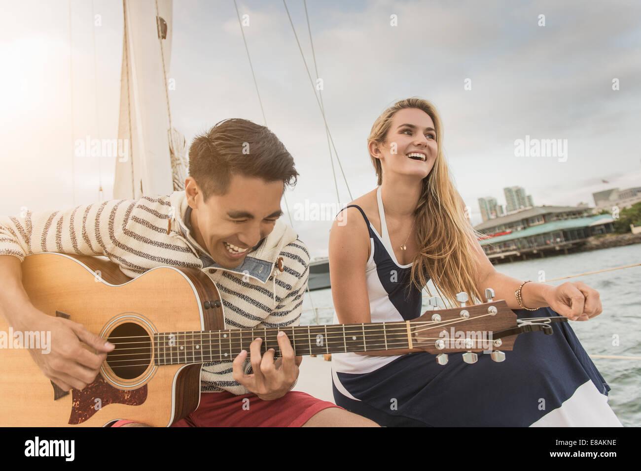 Jeune couple sur bateau à voile, man playing guitar Photo Stock