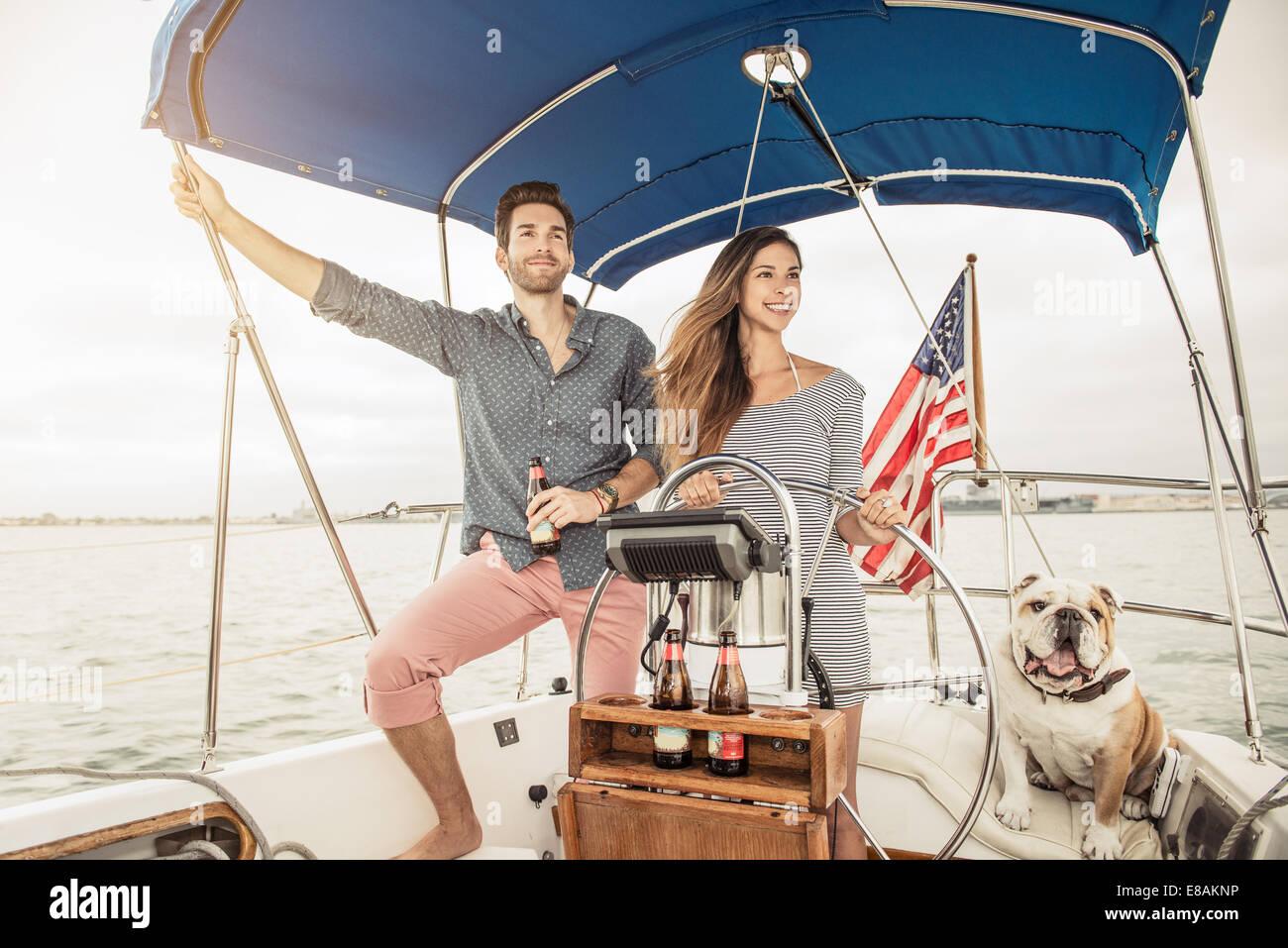 Couple sur bateau à voile avec chien Photo Stock