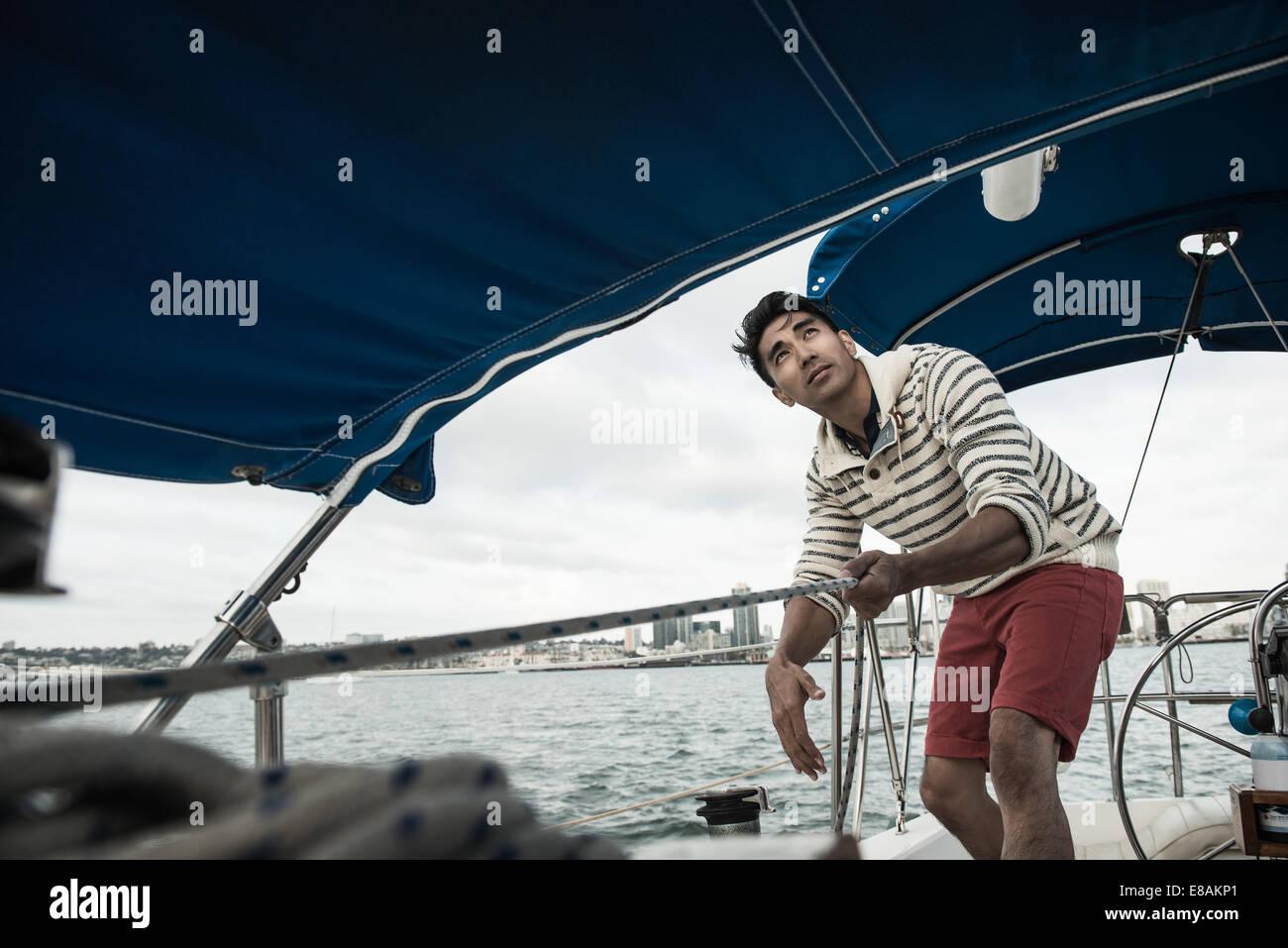 Jeune homme à la recherche jusqu'au bateau à voile Photo Stock