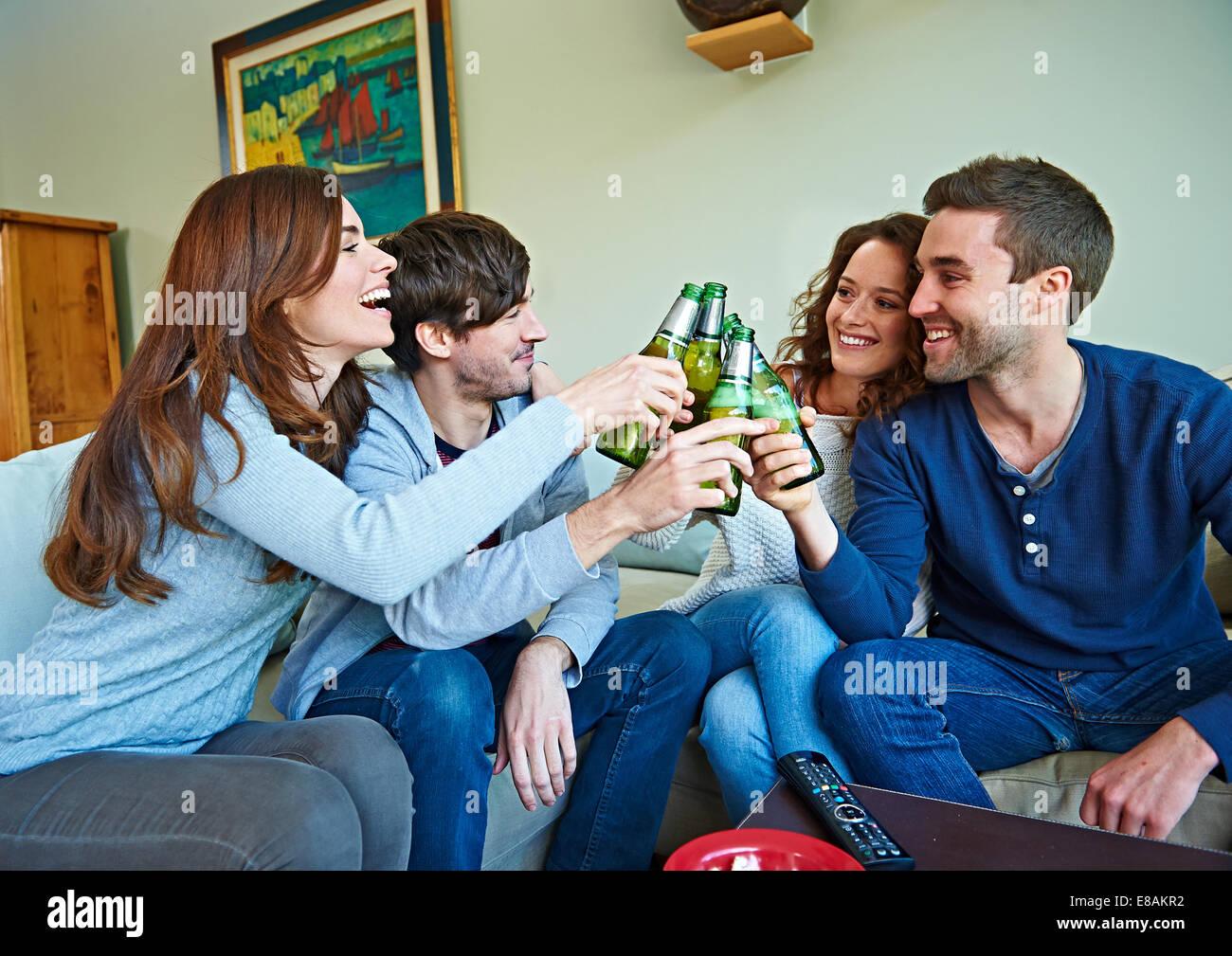 Groupe d'amis regarder les sports dans la salle de séjour Photo Stock
