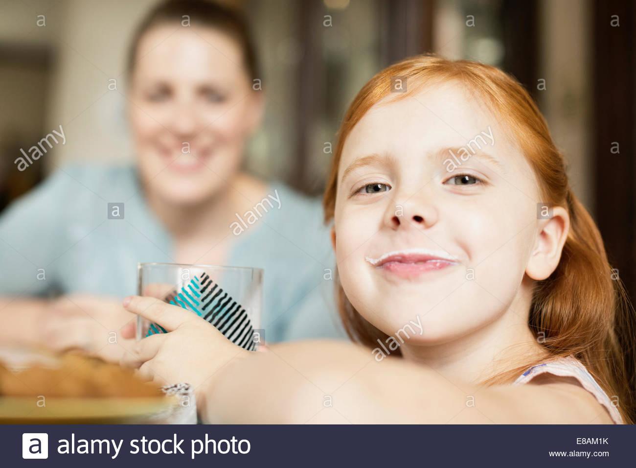 Fille avec une moustache de lait à table de salle à manger Photo Stock