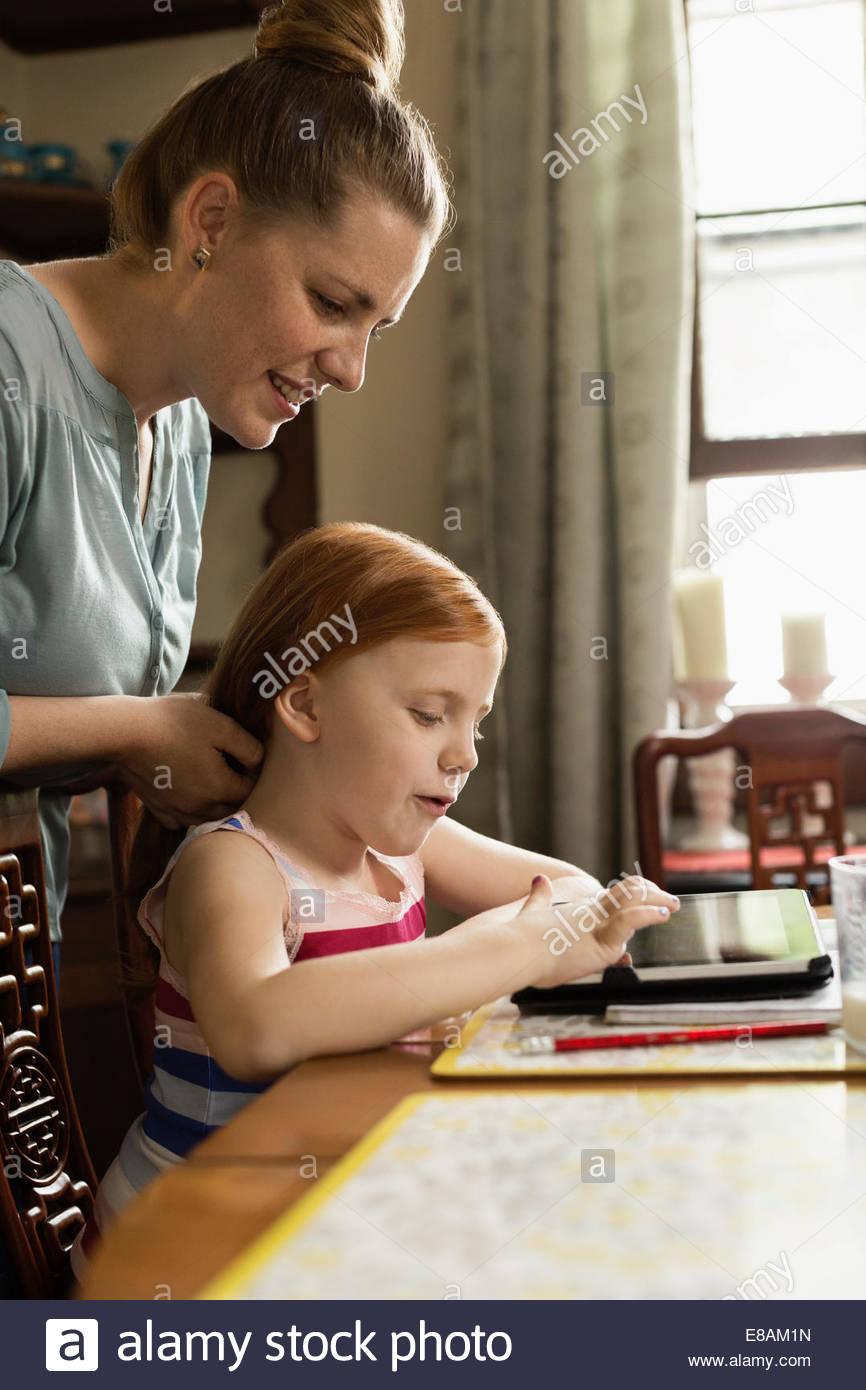 Girl using digital tablet à table de salle à manger tandis que ses cheveux styling mère Photo Stock