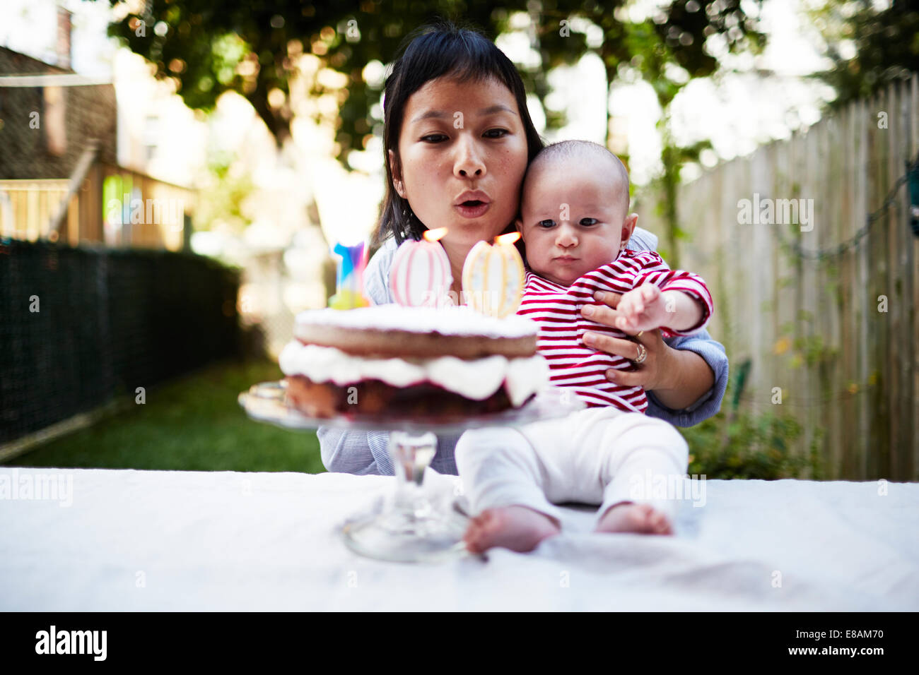 Mother holding baby fils, blowing out candles on cake Photo Stock