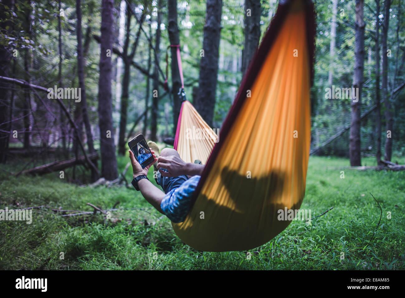 Randonneur couché dans un hamac en forêt à l'aide de l'appareil numérique Photo Stock