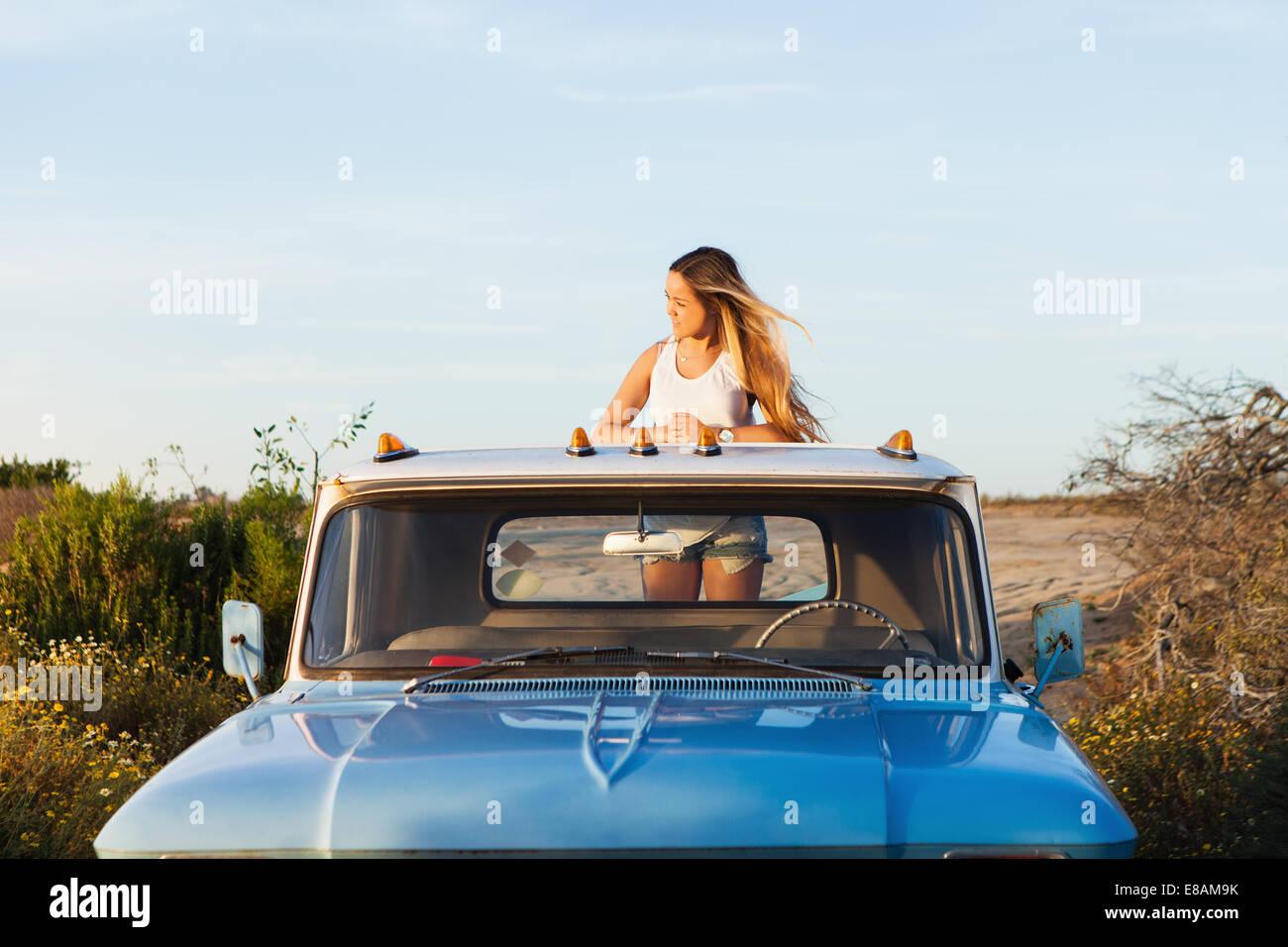 Jeune femme à la recherche de l'arrière d'un pick-up Banque D'Images