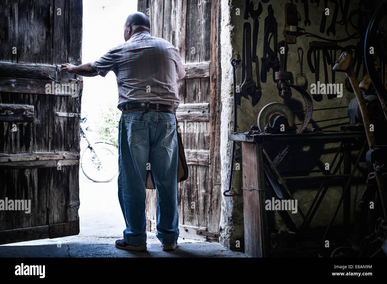 Vue arrière du senior male forgeron à l'ouverture des portes de grange traditionnelle, Cagliari, Sardaigne, Photo Stock