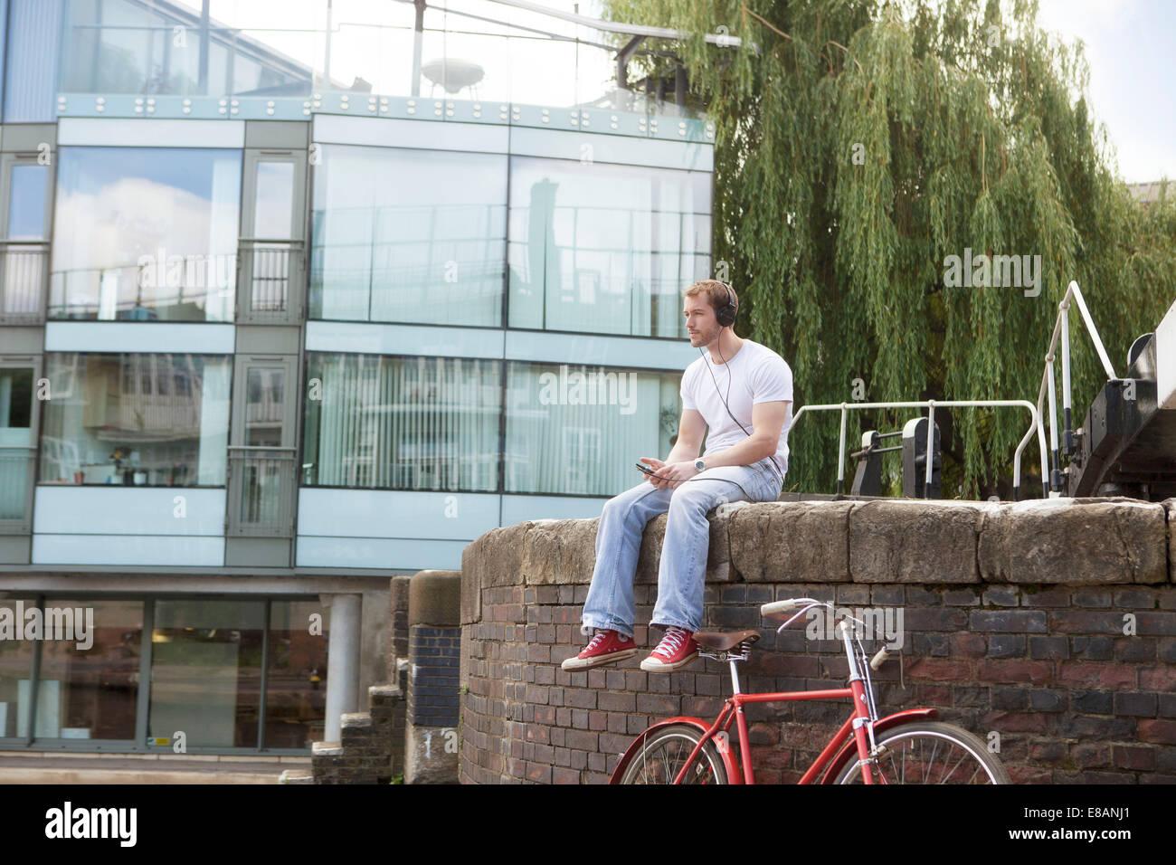 L'homme à écouter de la musique par canal, East London, UK Photo Stock
