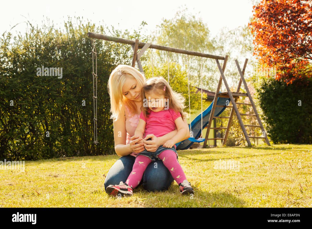 Mère et fille dans le jardin, des balançoires en arrière-plan Photo Stock