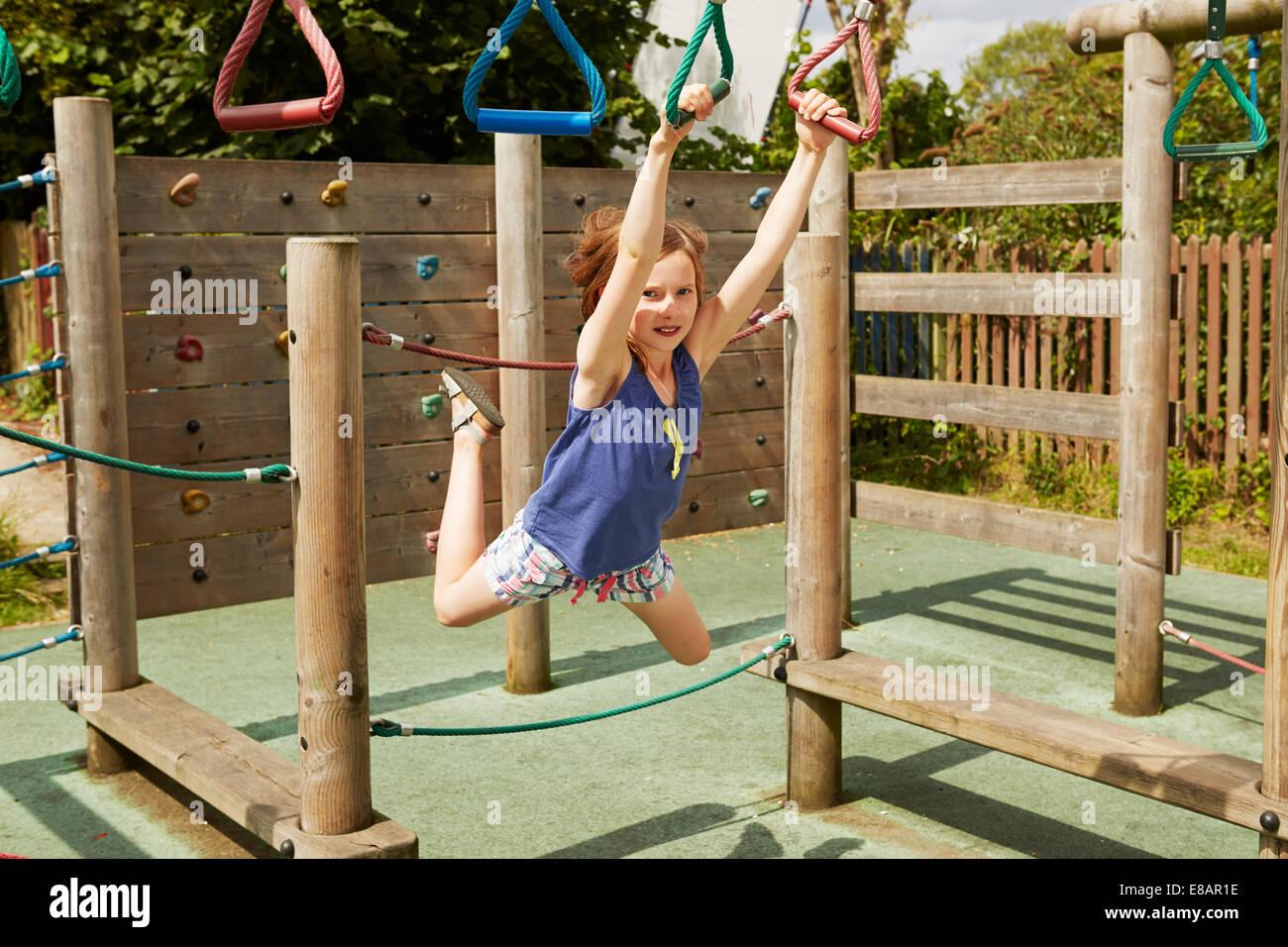 Fille énergique jouant sur des balançoires en aire de jeux Photo Stock