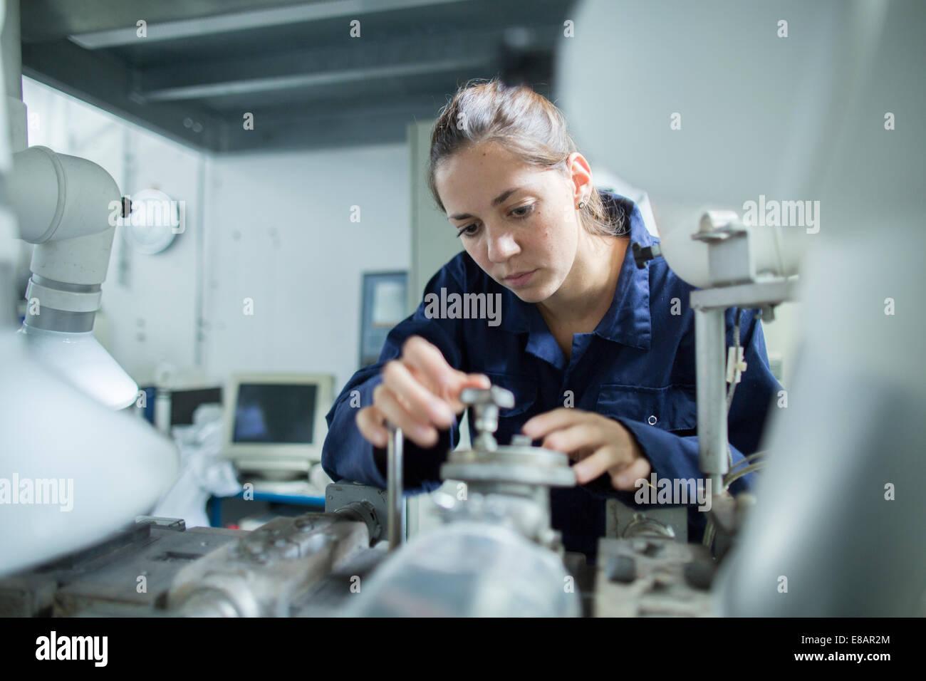 Ingénieur femelle tournant sur vannes tuyauterie industrielle en usine Photo Stock