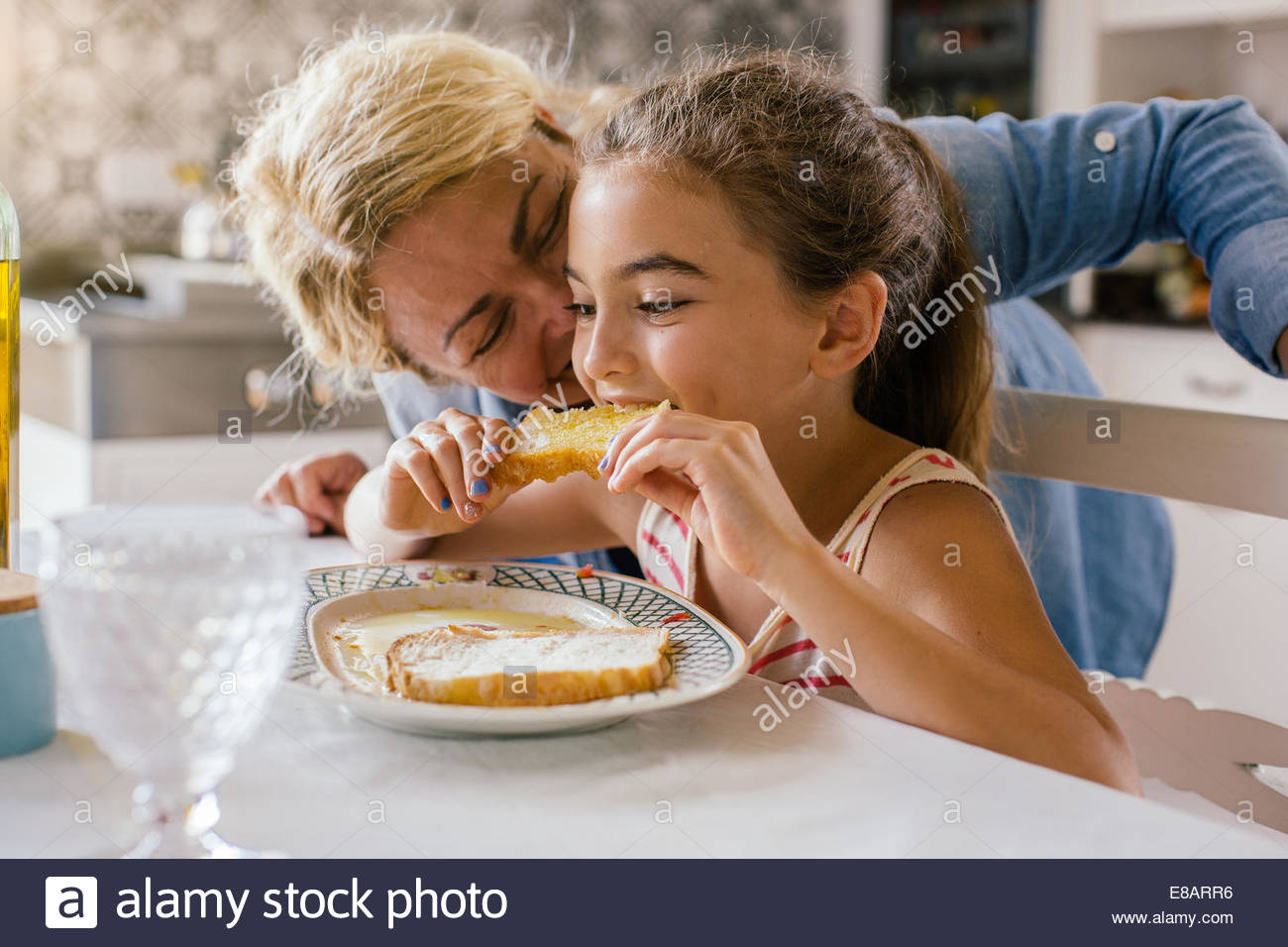 Girl eating toast avec grand-mère Photo Stock