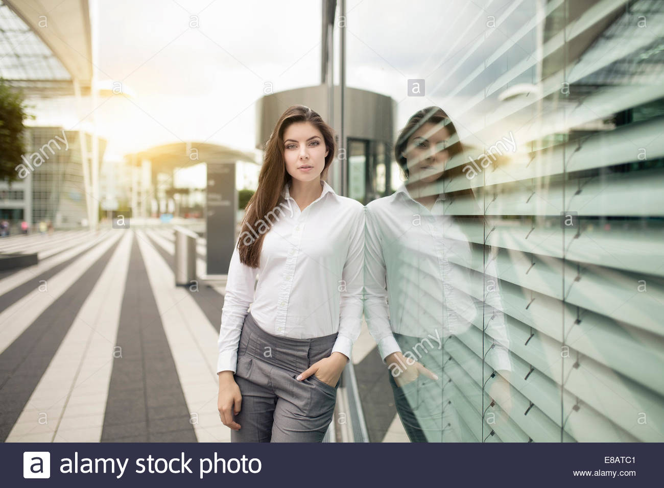 Businesswoman leaning against window, portrait Photo Stock