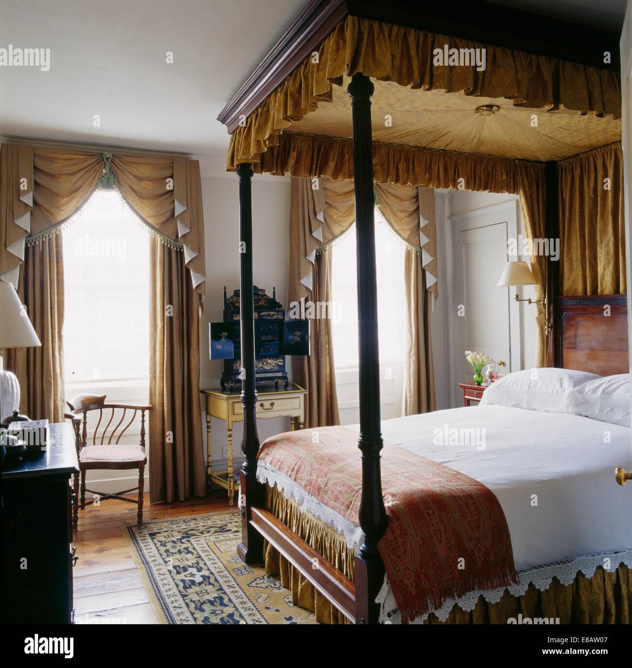 Un lit à baldaquin avec des rideaux de couleur beige et ...