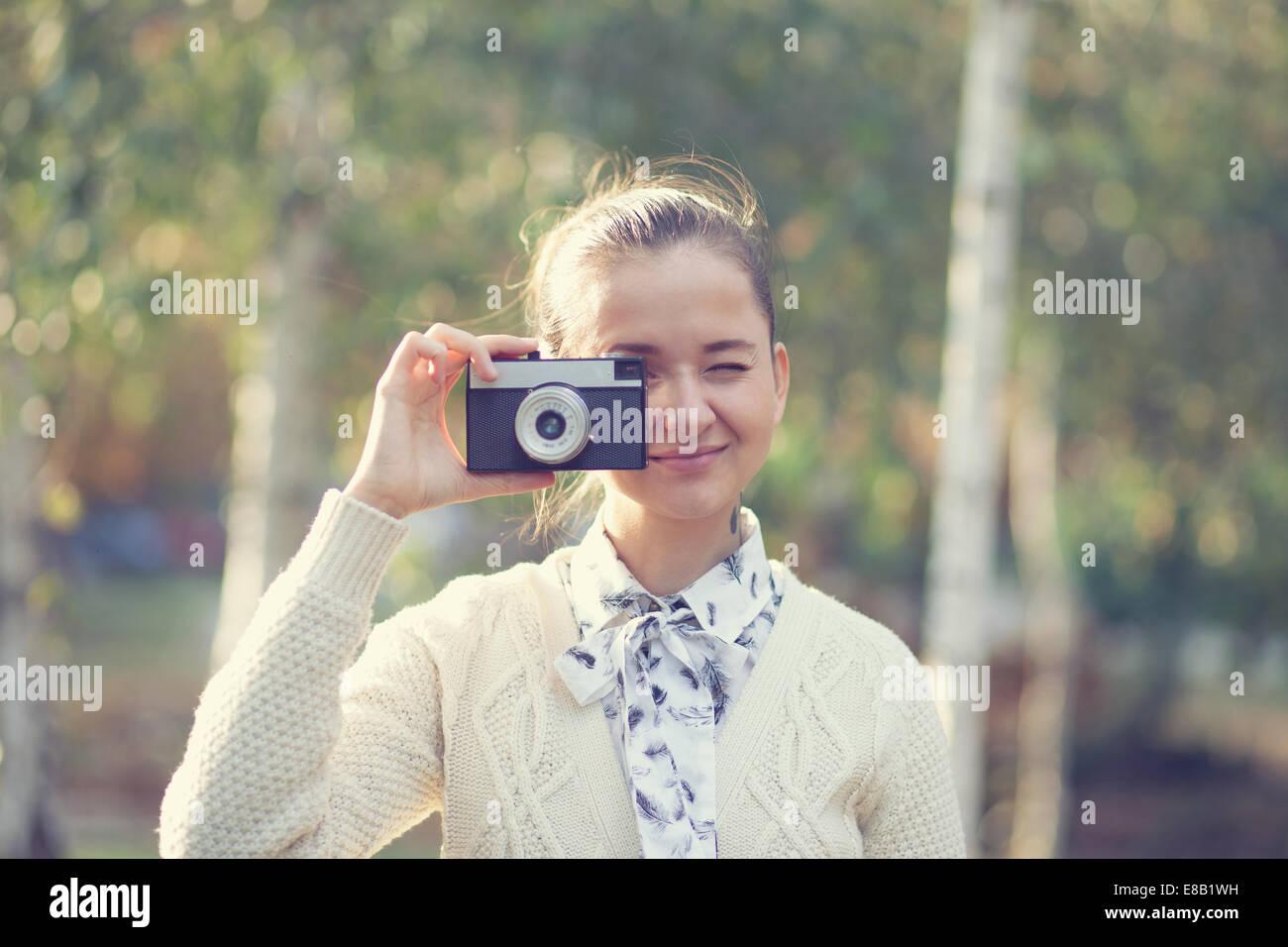 Hipster girl tournage sur film en plein air de l'appareil photo Photo Stock