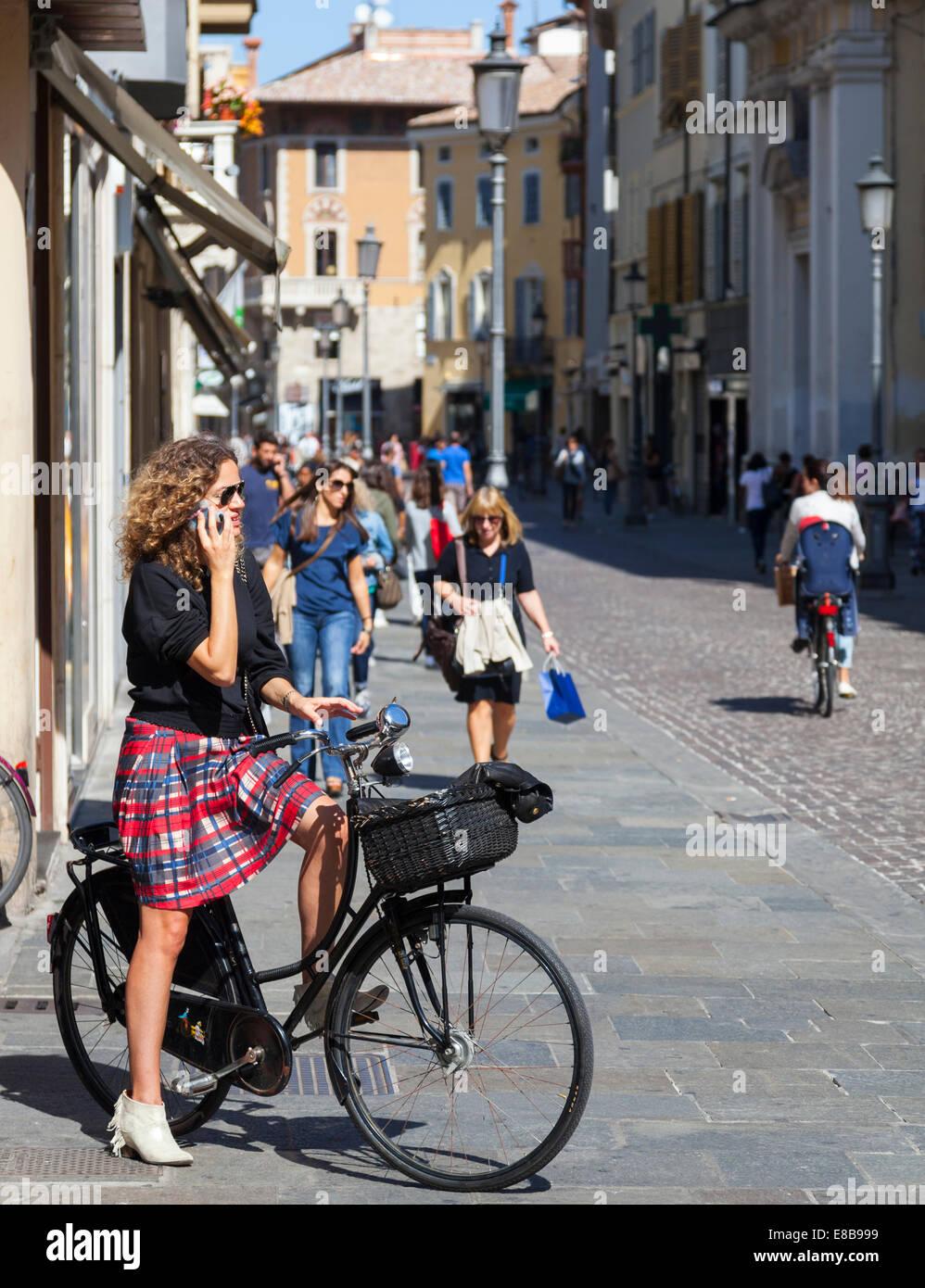 Jeune femme dans une jupe talking on mobile phone alors que sur une bicyclette, Parme, Emilie-Romagne, Italie Photo Stock