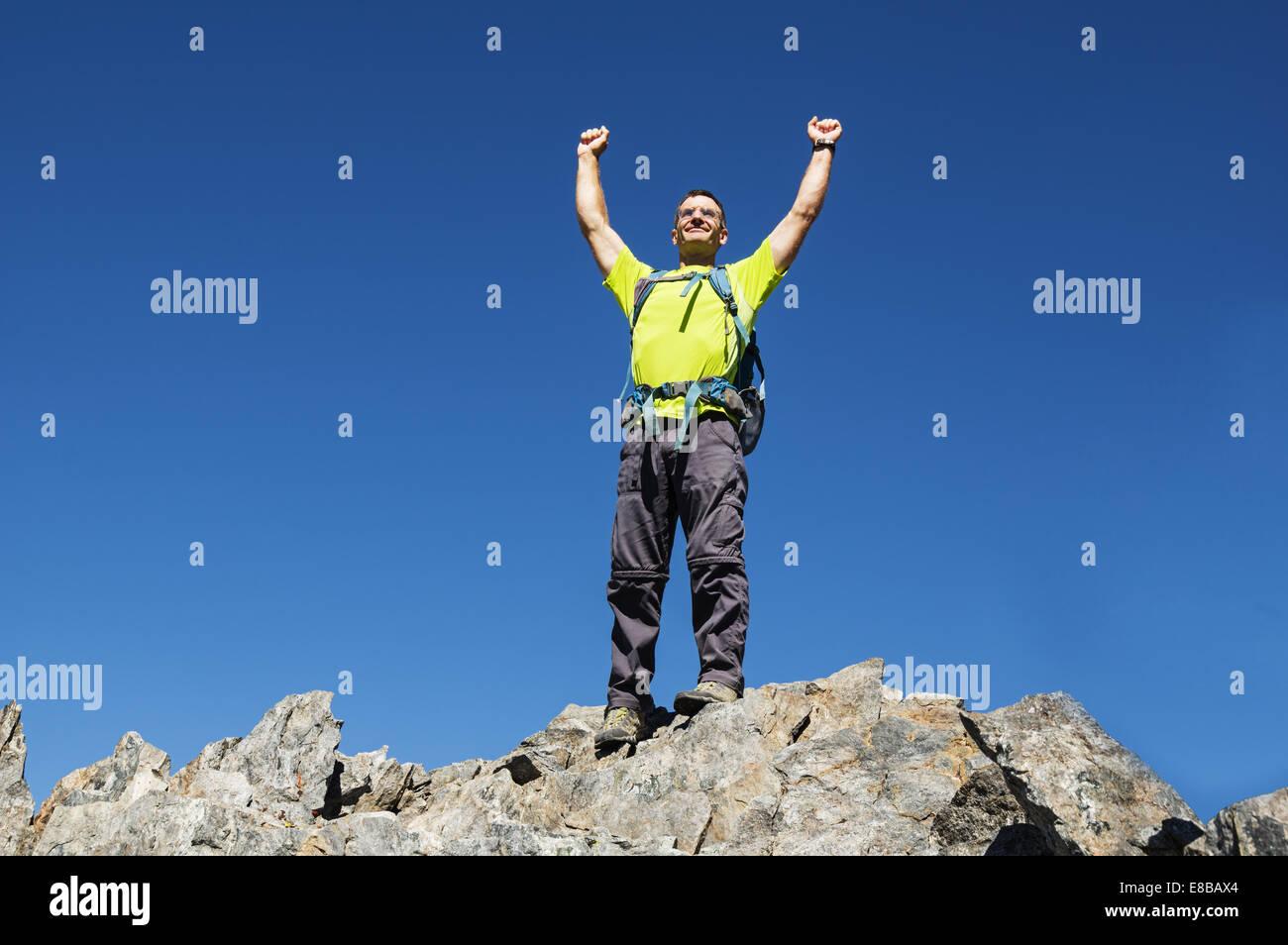 L'homme célèbre son succès au sommet du pic de Hurd en levant ses poings Photo Stock