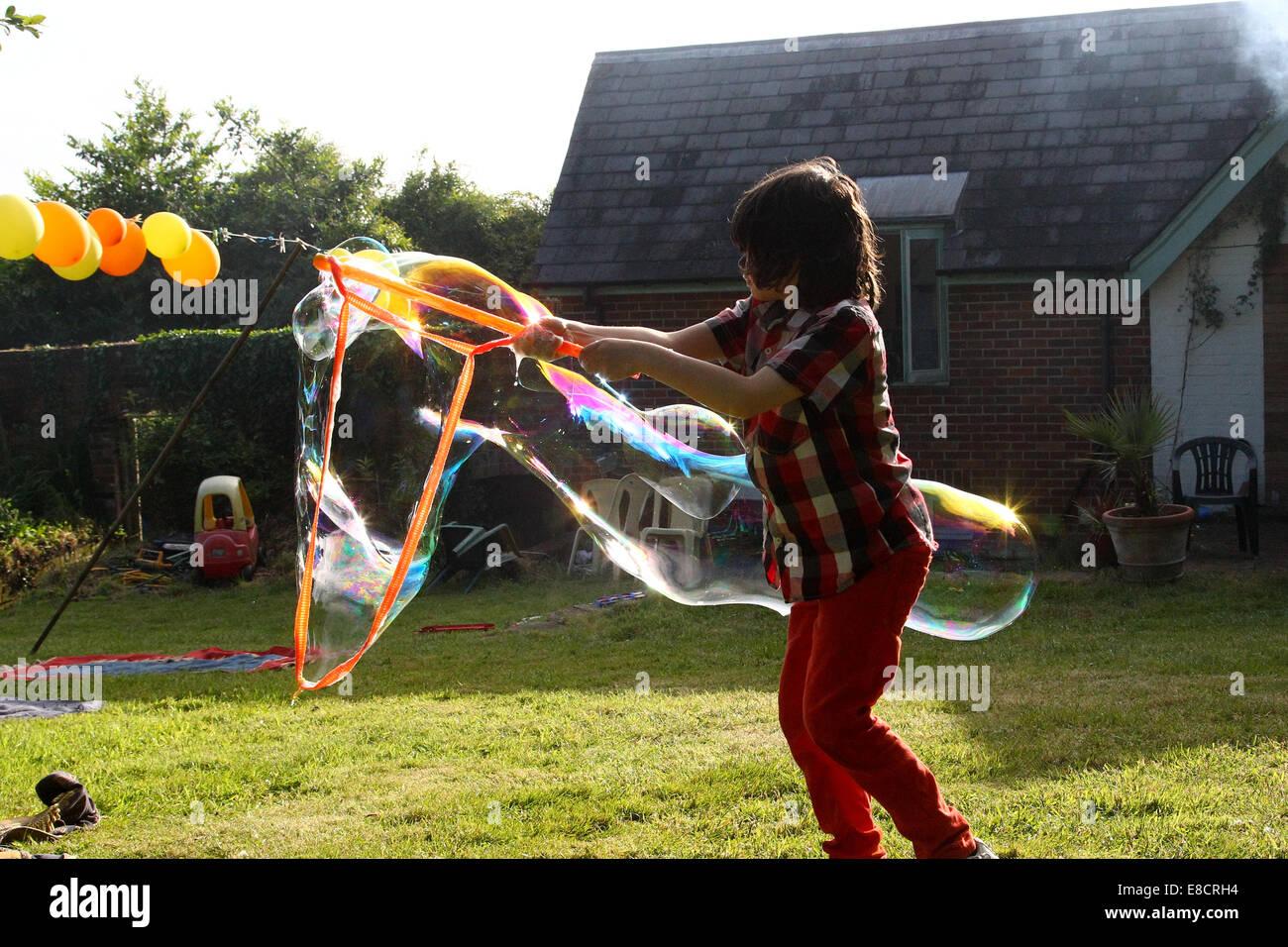 Un jeune enfant faire des bulles dans un jardin sur un jour d'été au cours d'une garden party. Photo Stock