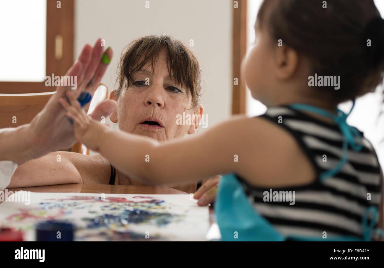 Grand-mère la peinture au doigt avec petit-enfant Photo Stock