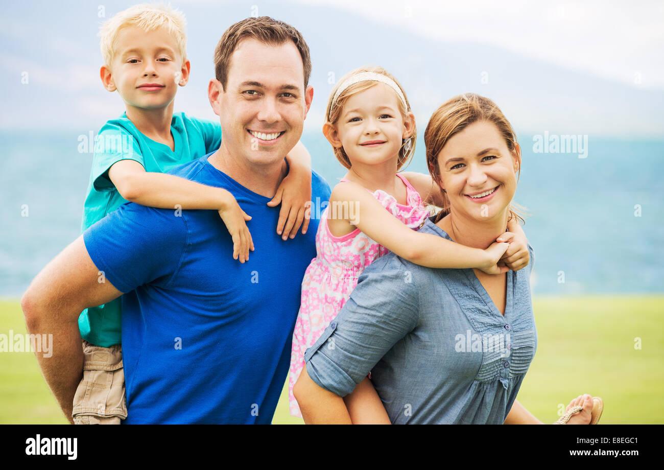 Portrait de famille heureuse de quatre à l'extérieur Photo Stock