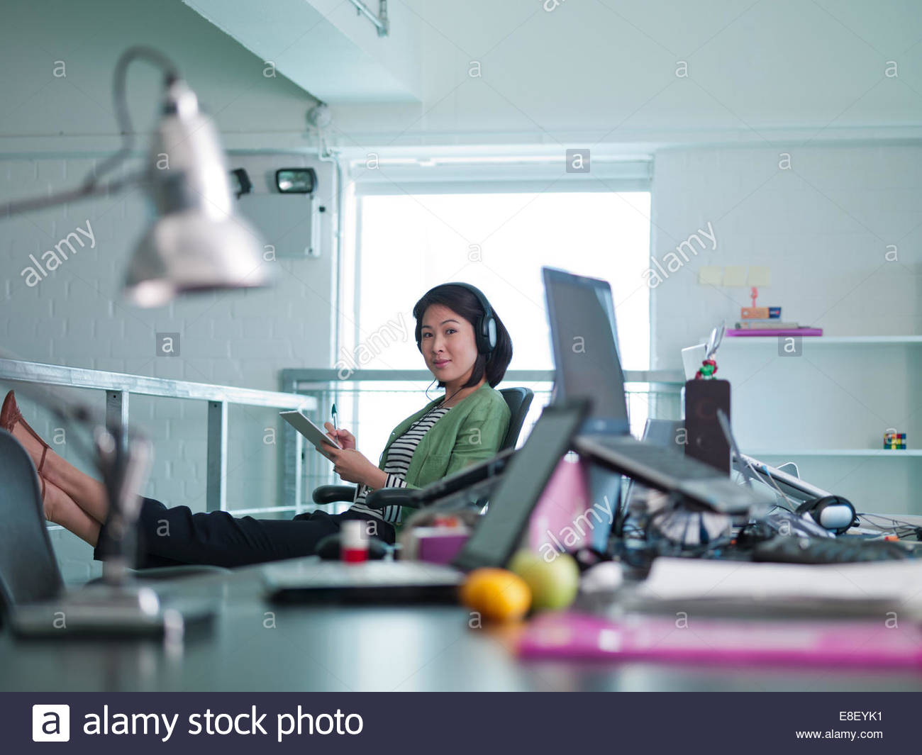 Businesswoman with headphones écrit sur l'application Notes in office Photo Stock