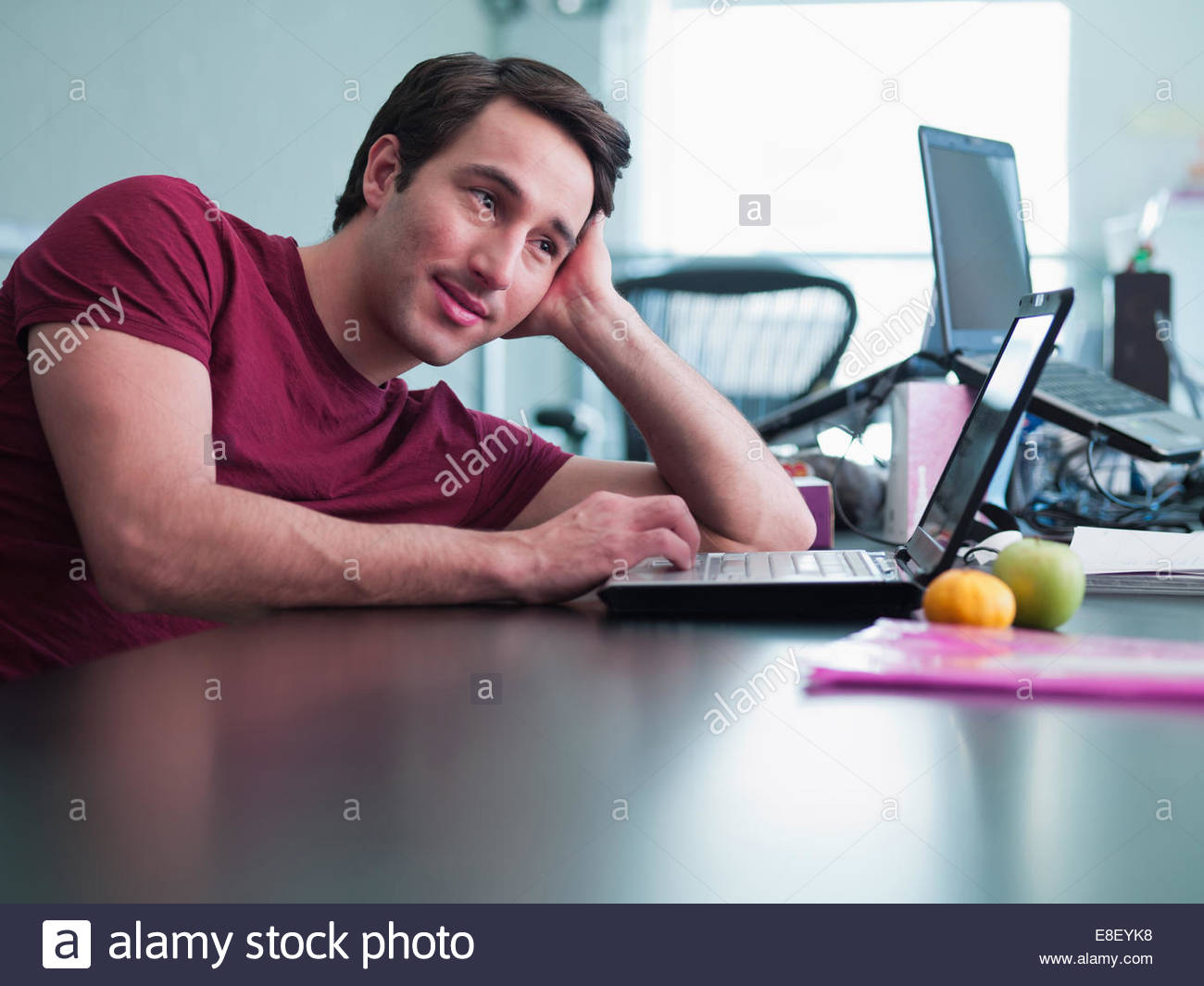 Smiling businessman using laptop and leaning on desk in office Photo Stock