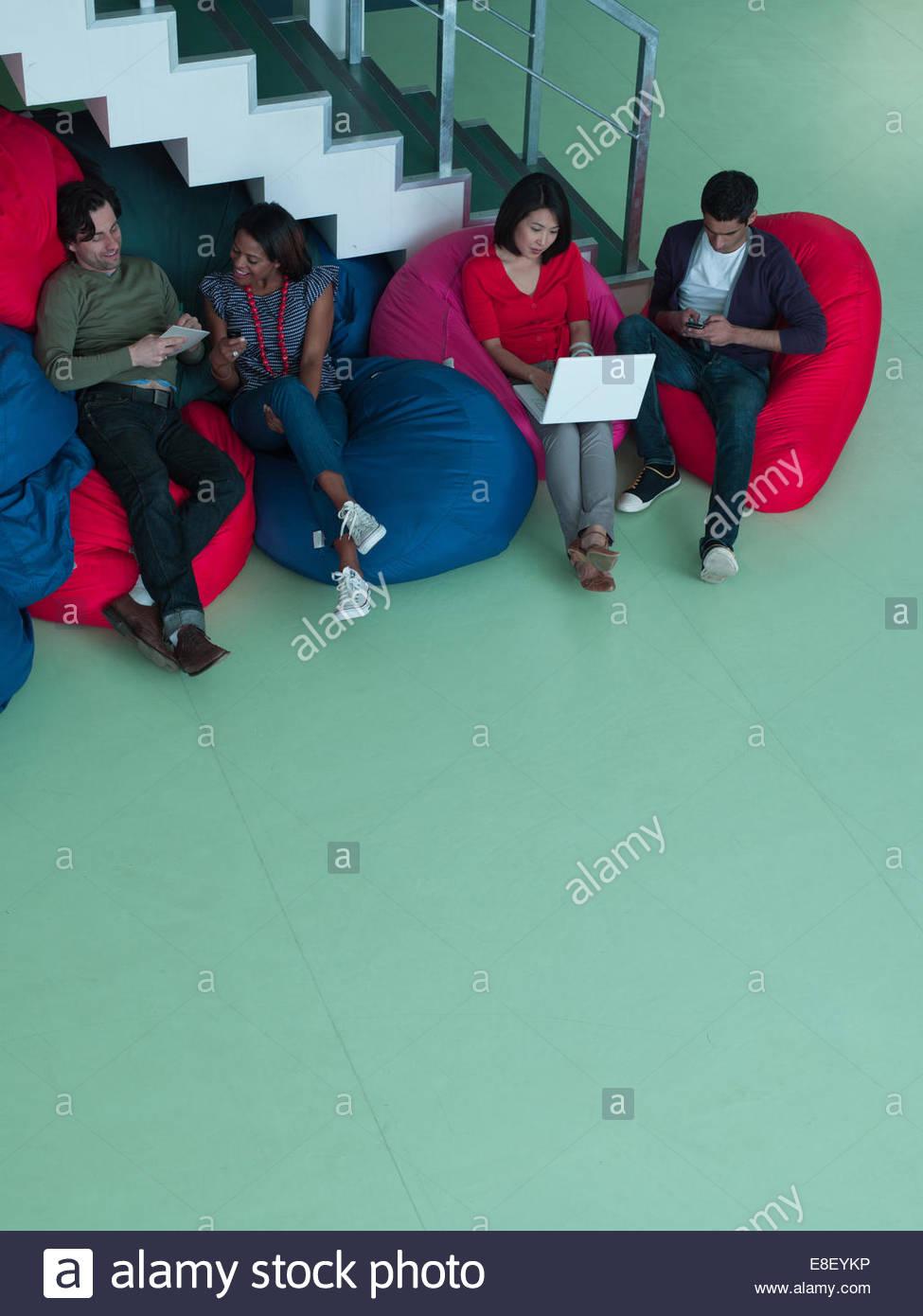 Les gens d'affaires dans des sièges-sacs looking at laptop Photo Stock
