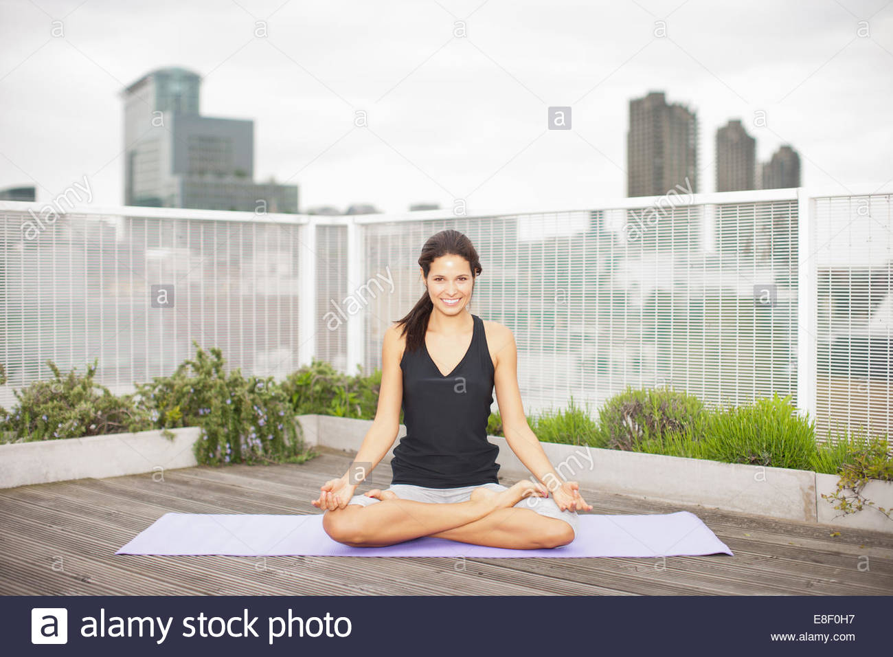 Woman practicing yoga on rooftop deck Photo Stock