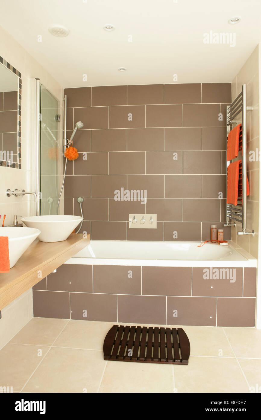 Carreaux marron sur le mur au-dessus de baignoire avec ...