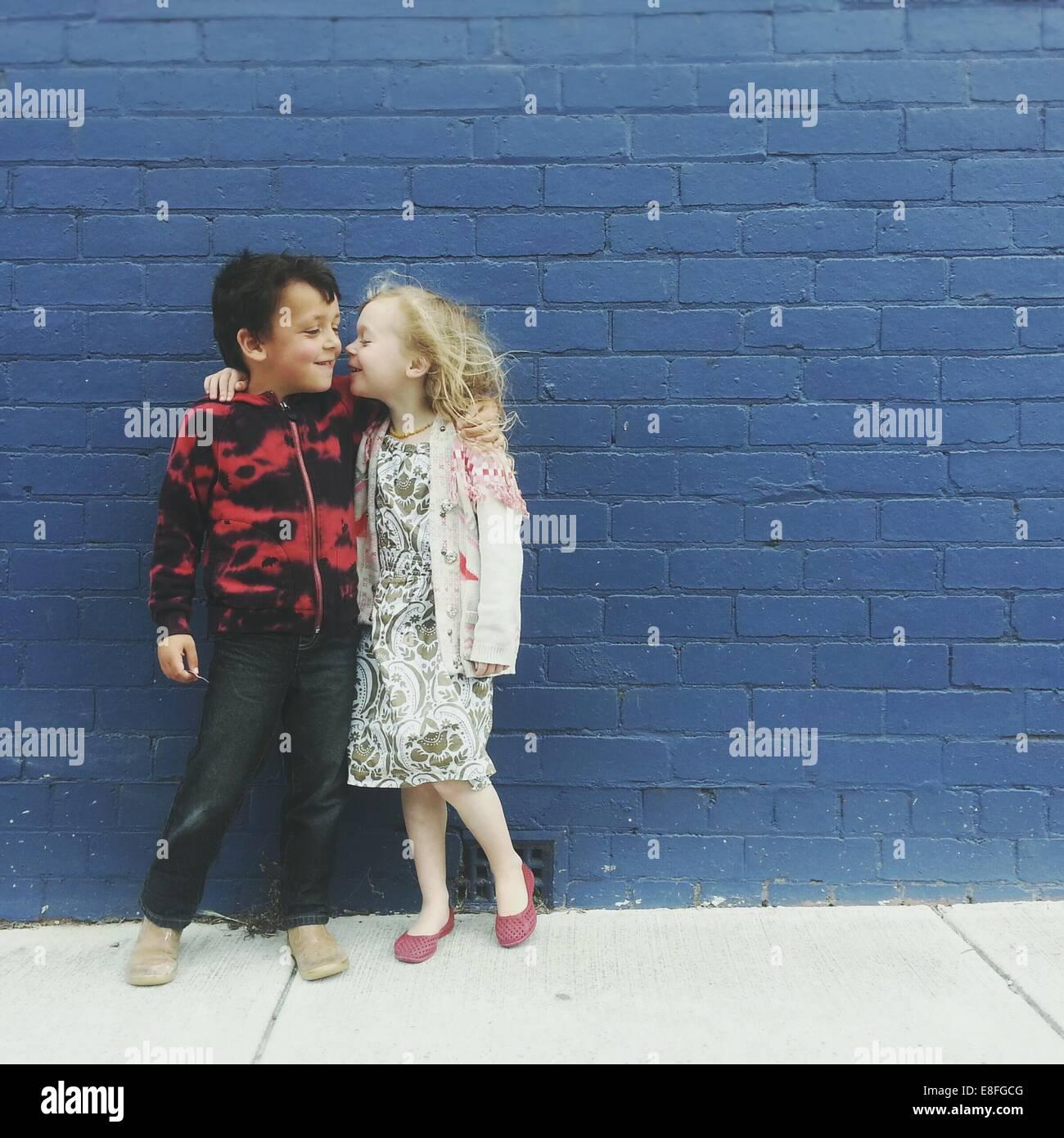 Garçon et fille avec leurs bras autour de l'autre Photo Stock
