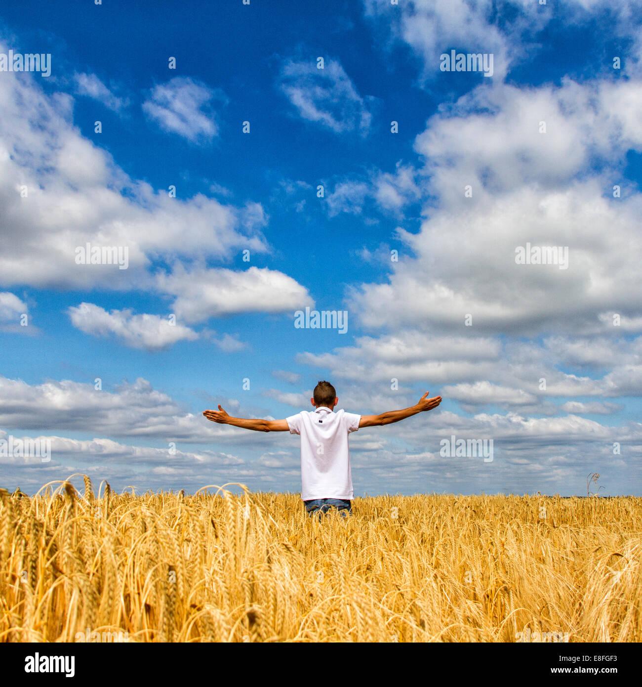 Vue arrière de l'Homme debout dans le champ avec les bras tendus Photo Stock