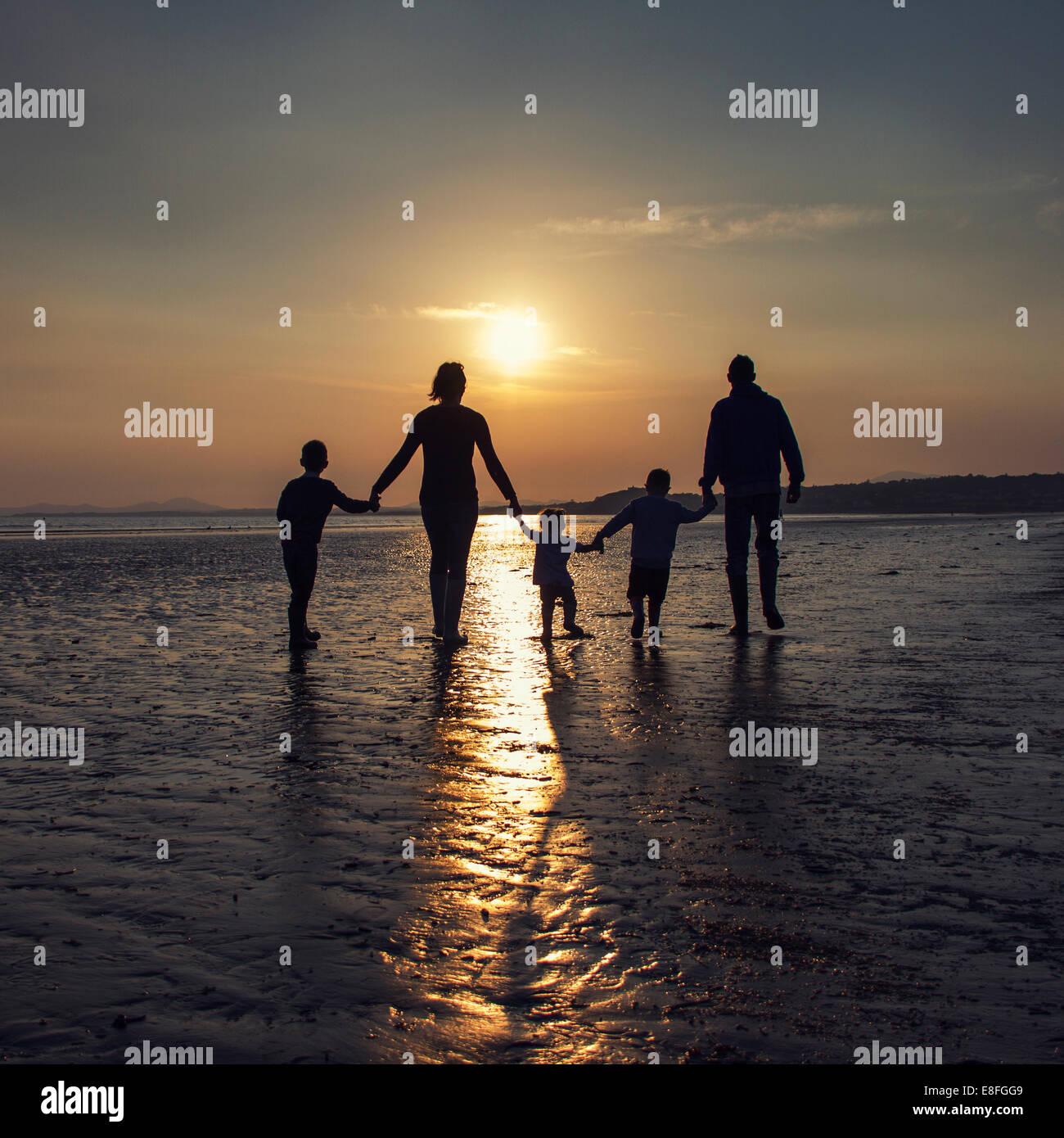 Silhouette d'une famille sur la plage holding hands Photo Stock