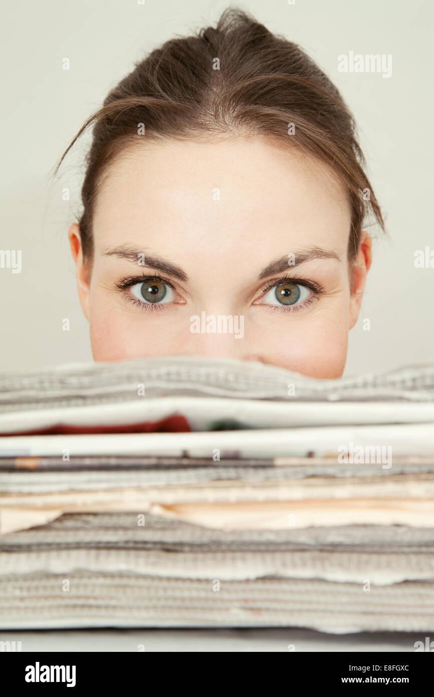 Tête de jeune femme à la recherche sur le haut d'une pile de journaux Photo Stock