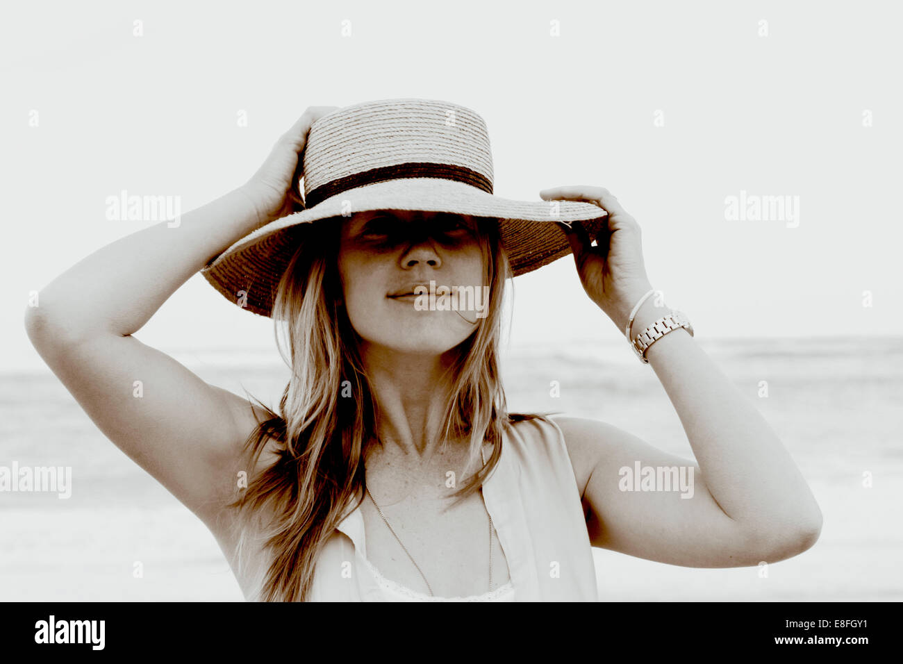 Portrait of a woman standing on beach holding her hat Photo Stock