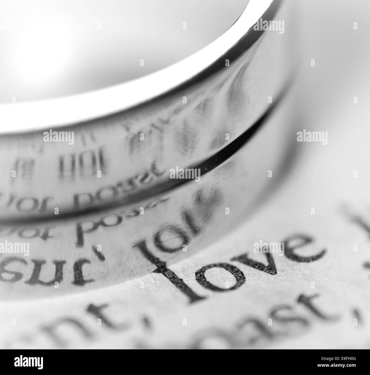 Close-up de l'anneau de mariage sur papier avec le mot amour Photo Stock