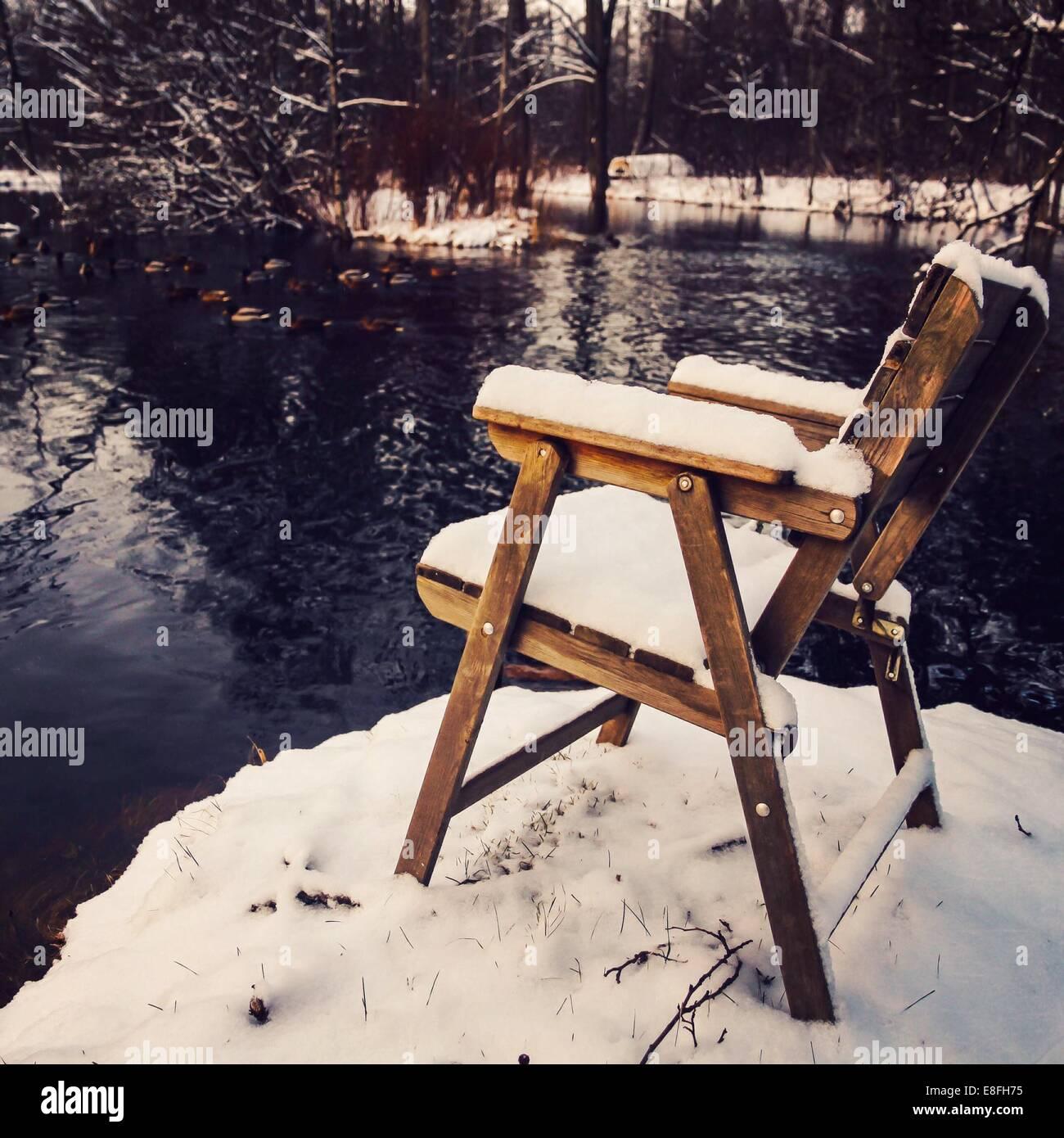 Chaise couverts de neige en hiver par le lac Photo Stock