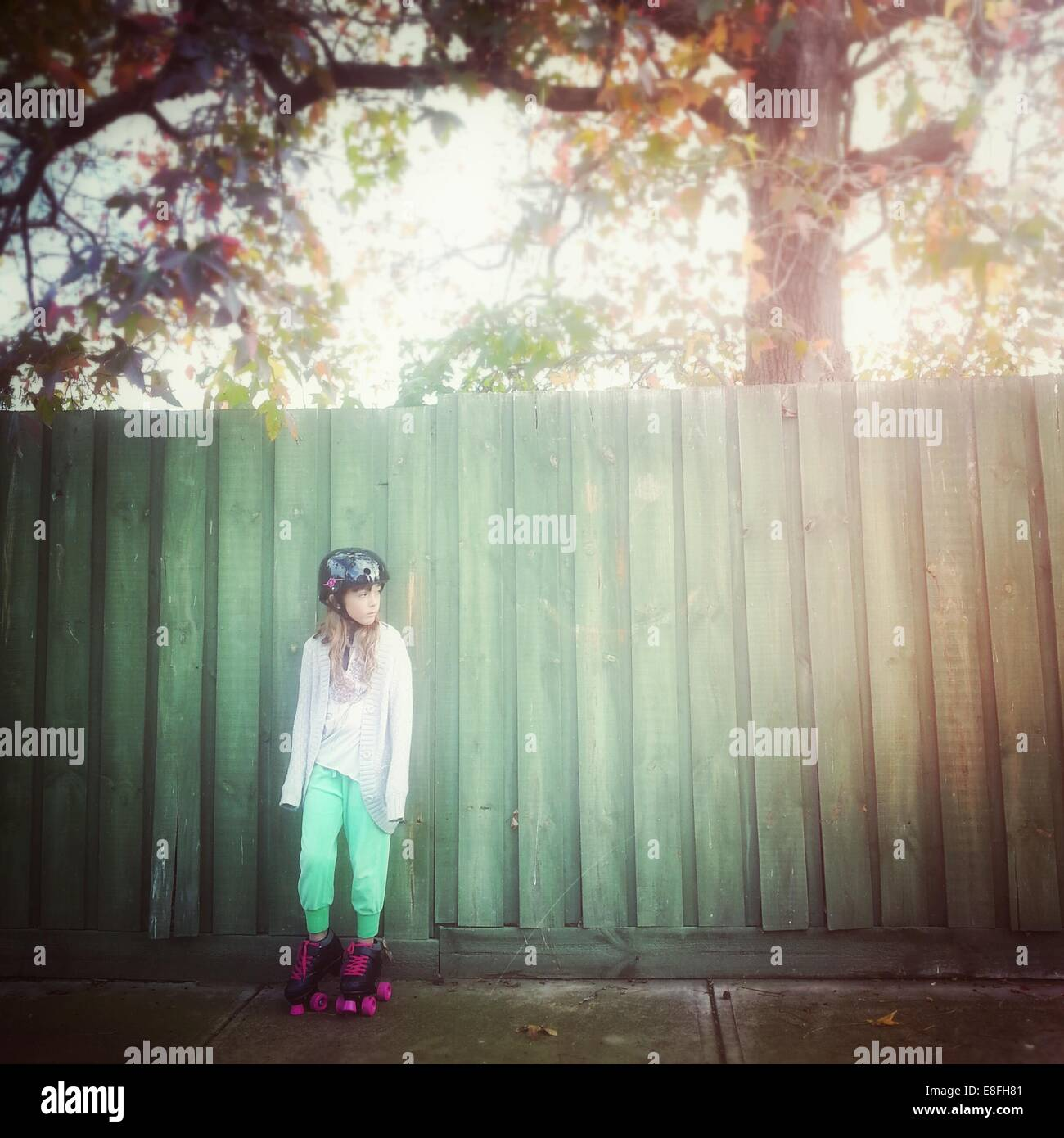 Girl wearing rollerskates leaning against fence Photo Stock