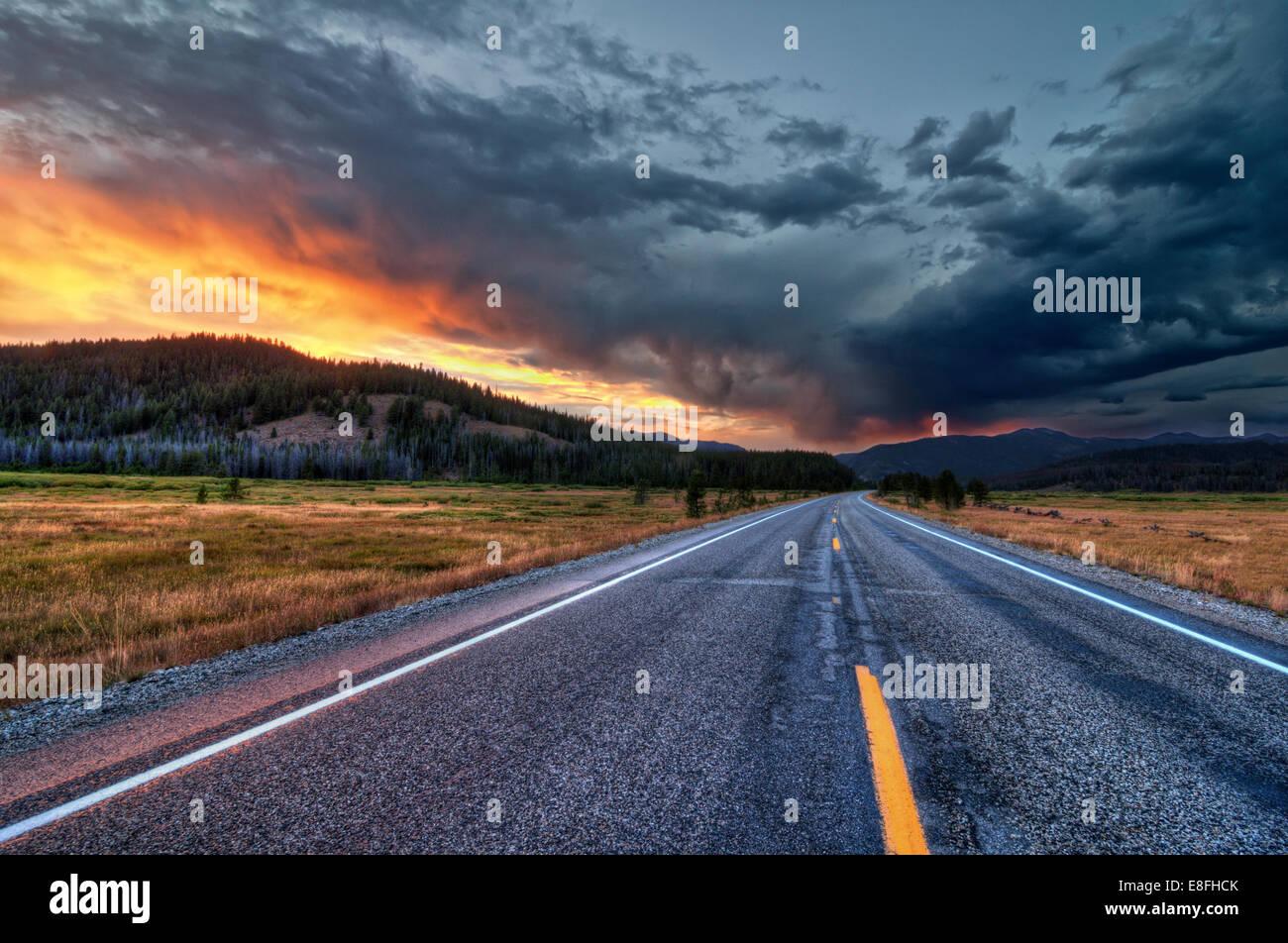 Route droite au coucher du soleil Photo Stock