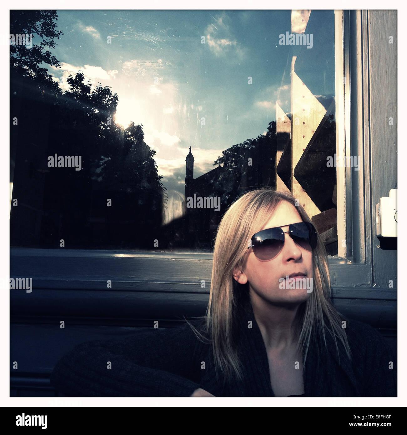 Portrait d'une femme assise devant une fenêtre au soleil Photo Stock