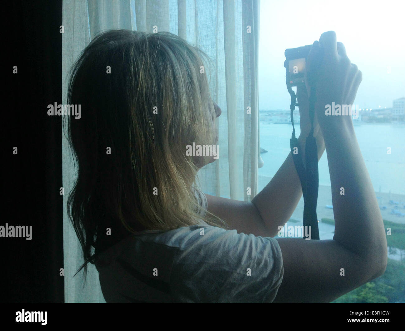 Woman taking photograph hors de la fenêtre Photo Stock