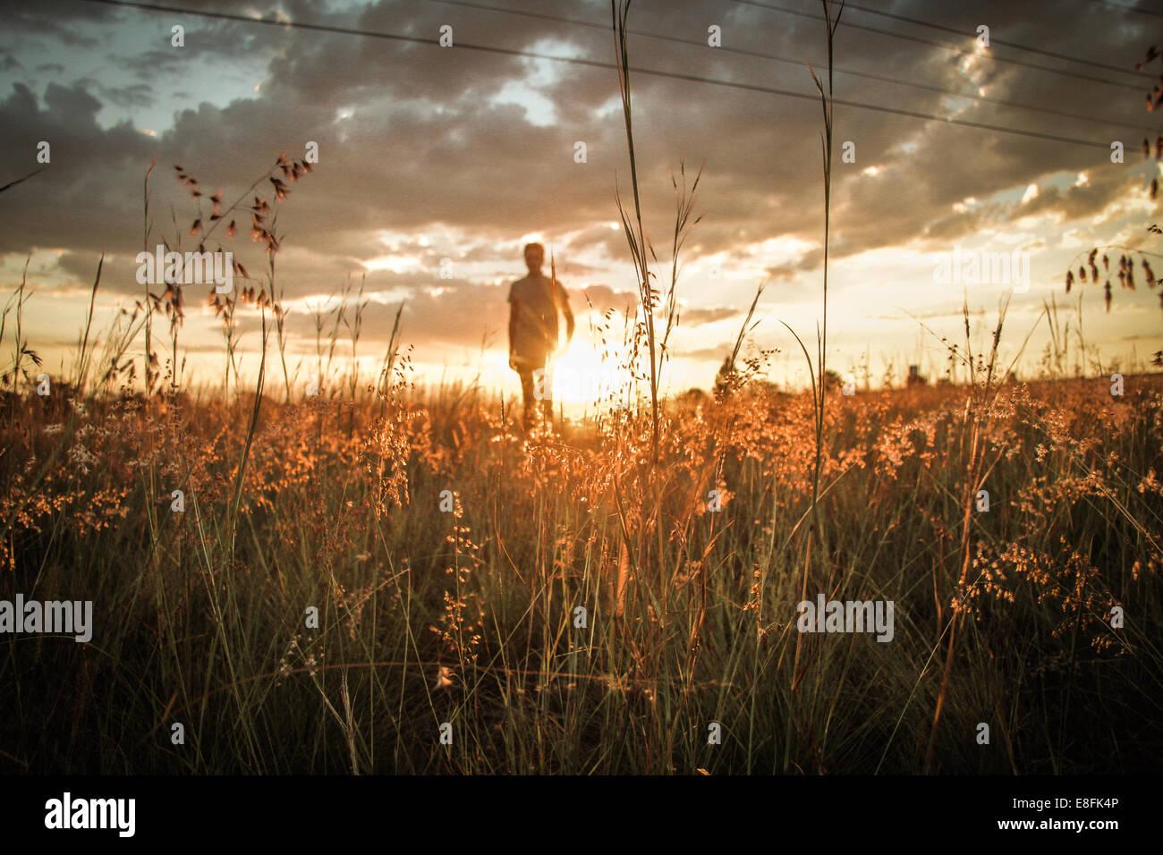 Homme de terrain comme le coucher du soleil Photo Stock