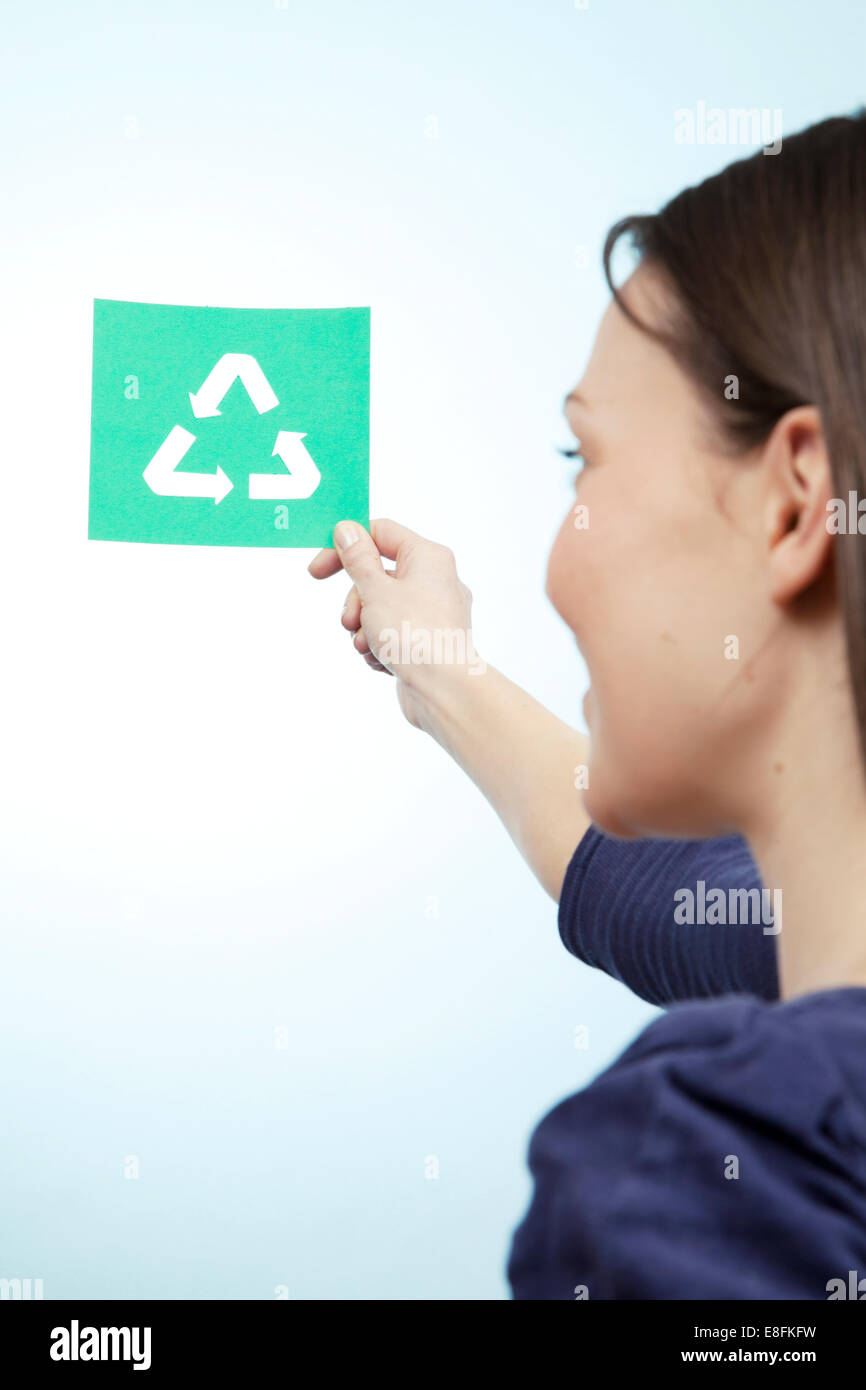Woman holding paper cut out of recycling symbol Photo Stock
