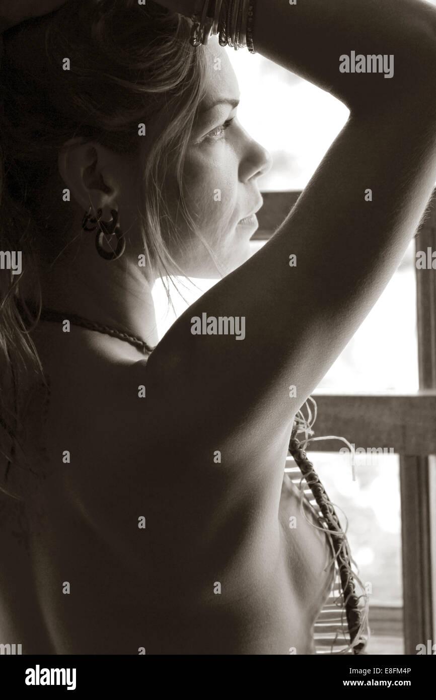 Portrait d'une femme debout par une fenêtre avec ses bras levés Banque D'Images