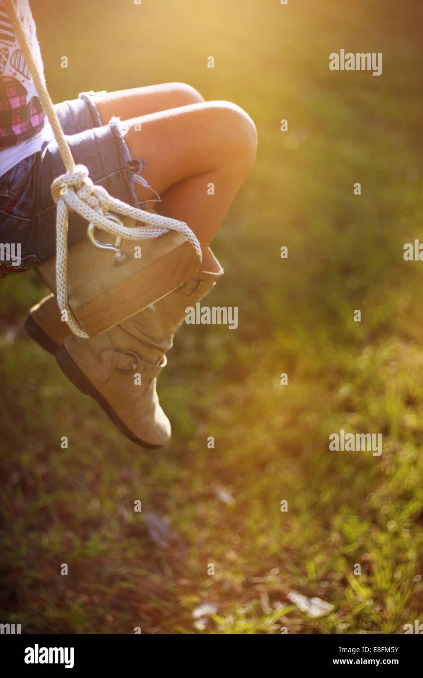 Gros plan sur les jambes d'une fille assise sur une balançoire de corde dans le jardin, Mississippi, États-Unis Banque D'Images