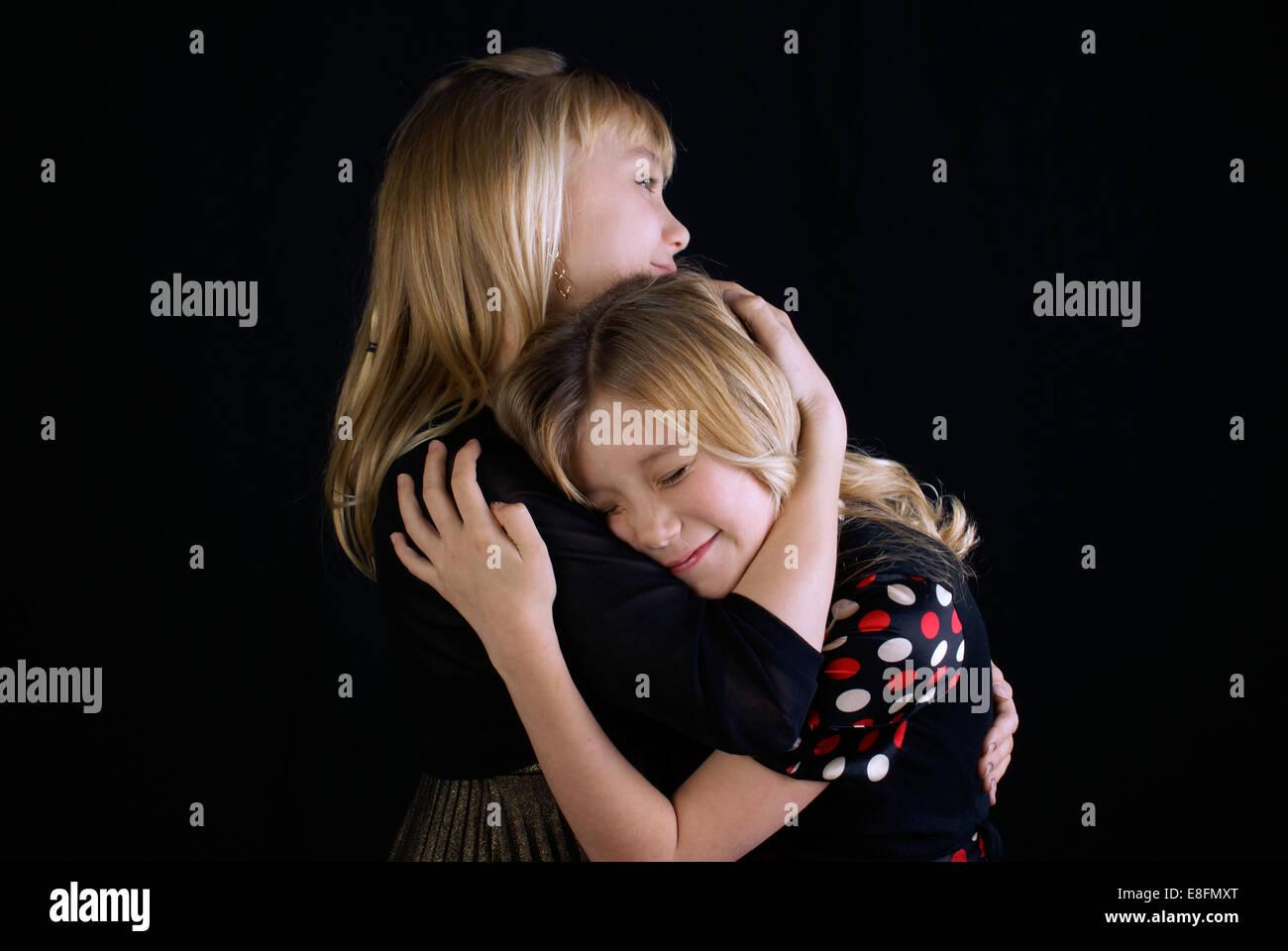 Portrait de deux soeurs (12-13, 16-17) hugging Banque D'Images