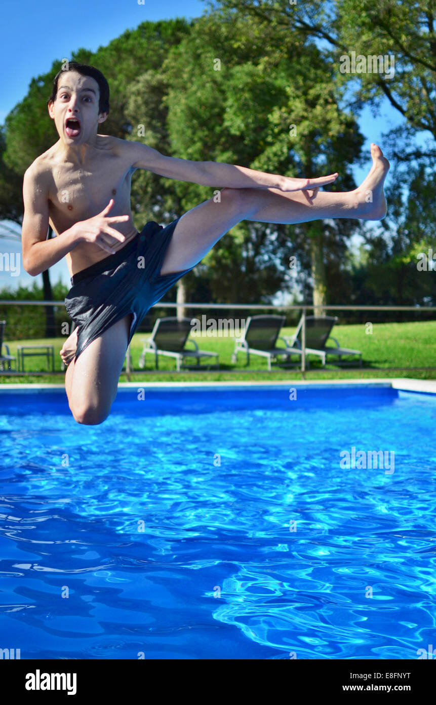 Boy jumping into swimming pool Photo Stock