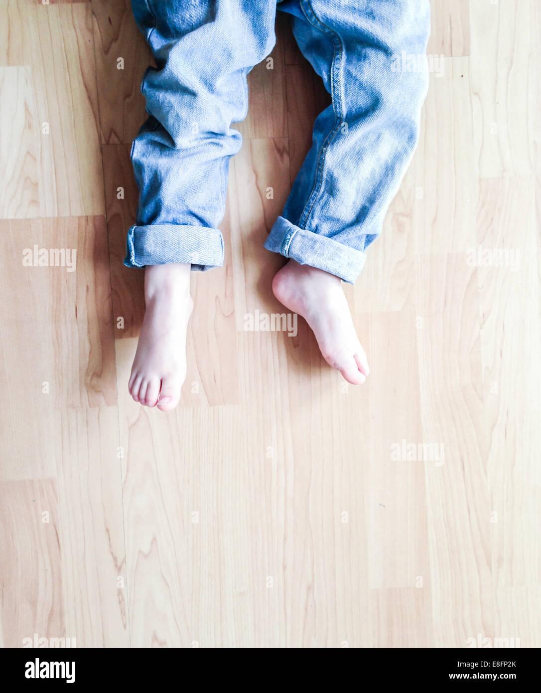 Vue de dessus de jambes du garçon lying on floor Photo Stock