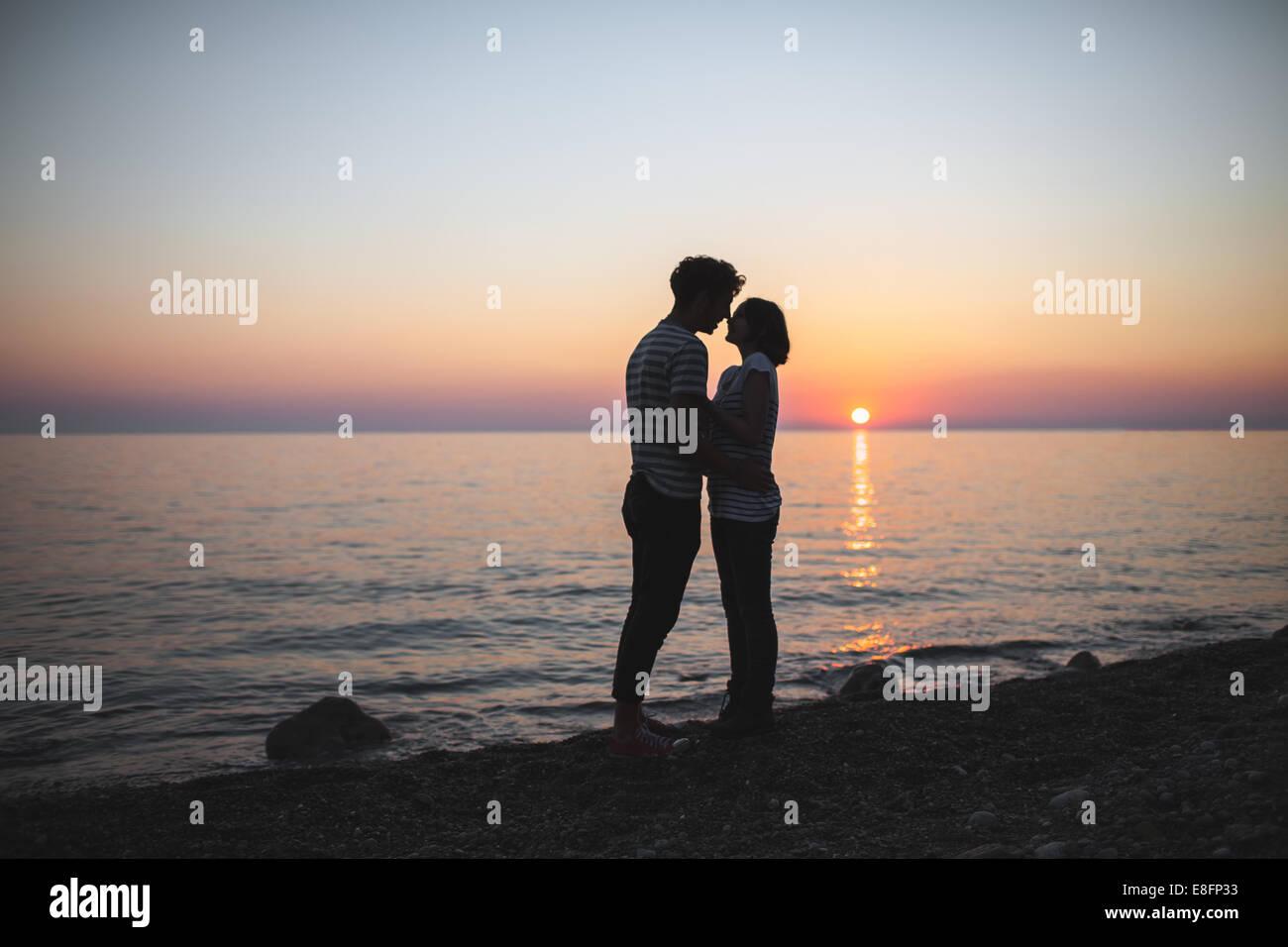 Adolescents (14-15) serrant les uns les autres au coucher du soleil Photo Stock