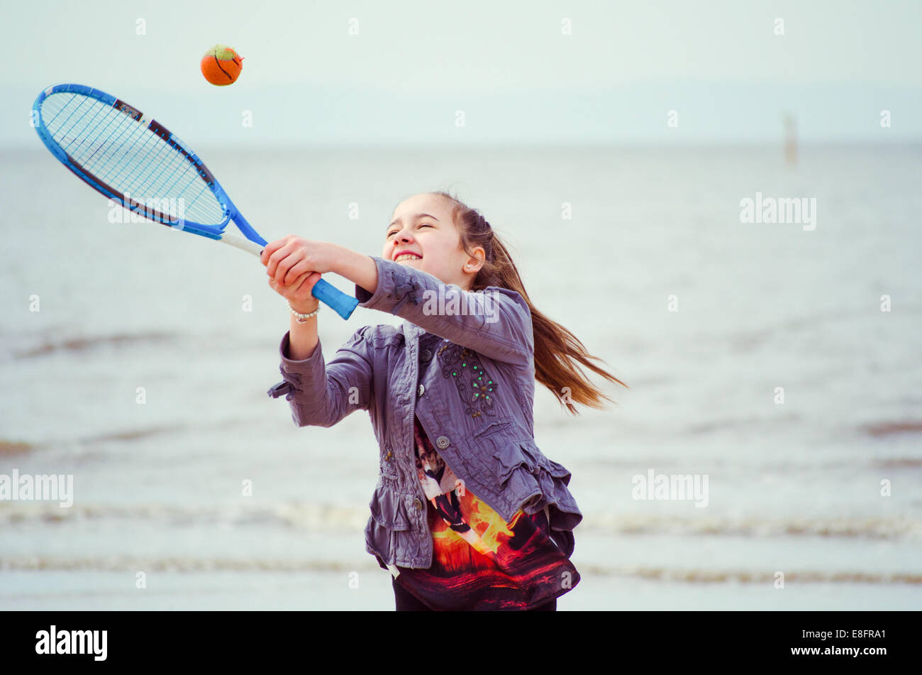 Fille jouant au tennis sur la plage Photo Stock