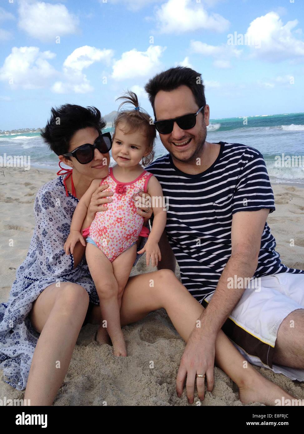 Mère, père et fille (18-23 mois) sitting on beach Banque D'Images
